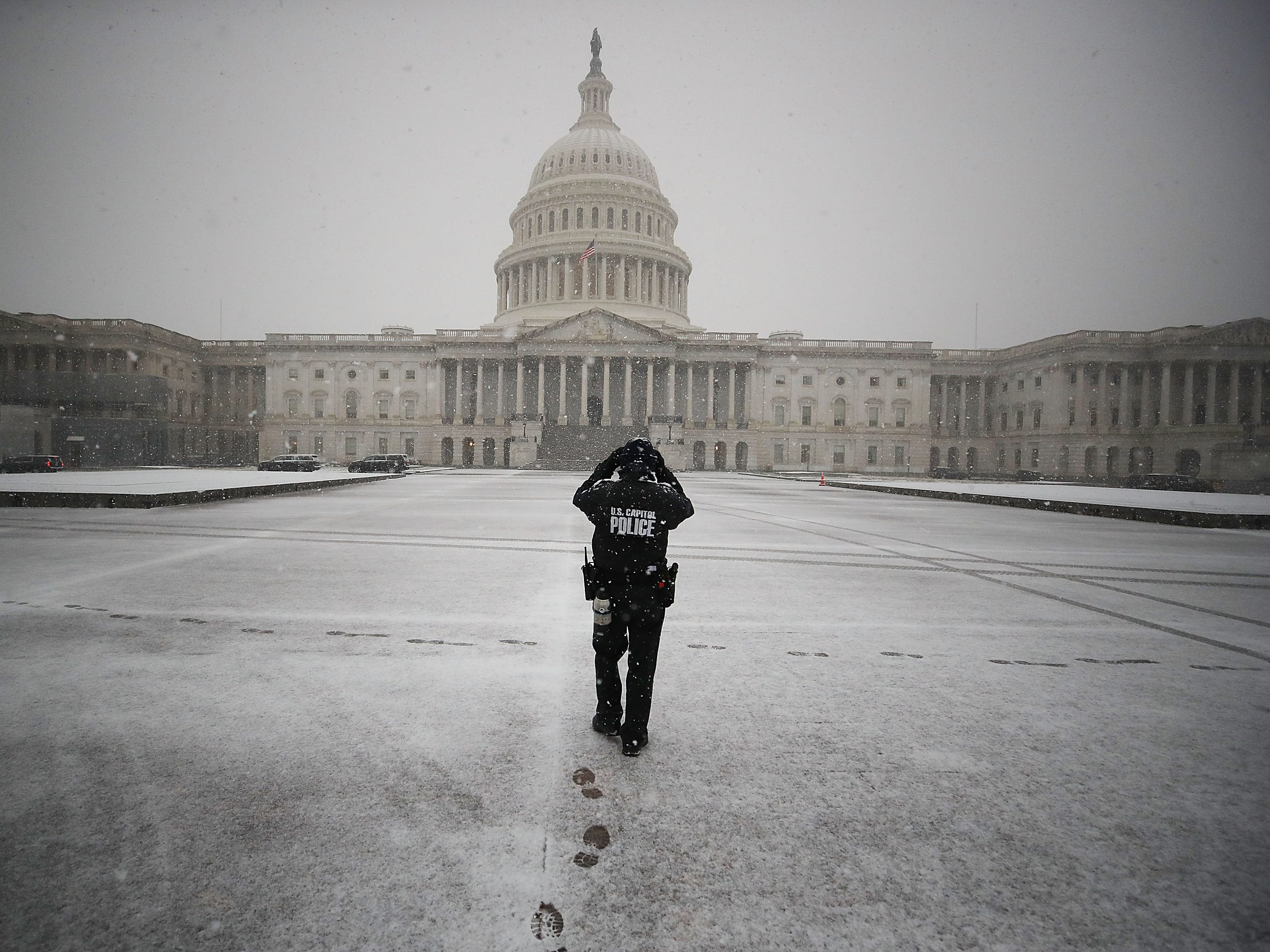 A U.S. Capitol Police Officer patrols the Capitol plaza as snow falls on Nov.15, 2018, in Washington.