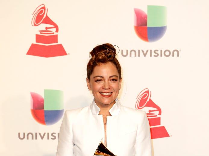 Natalia Lafourcade holds the trophy for Best Folk Album.