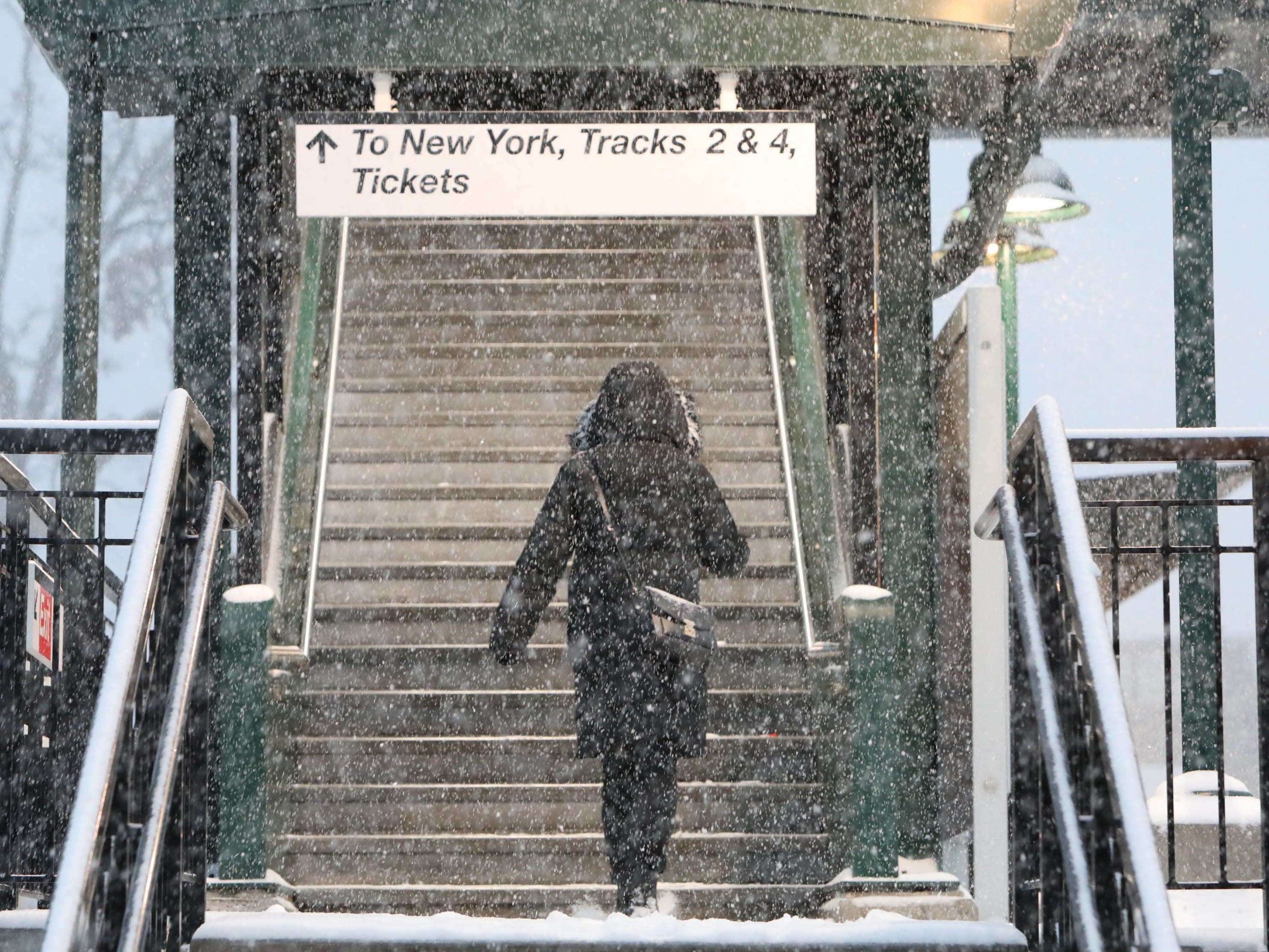 A Metro-North commuter takes the stairs to the New York City bound platform at the train station in Tarrytown, N.Y. during a steady snowfall Nov. 15, 2108.