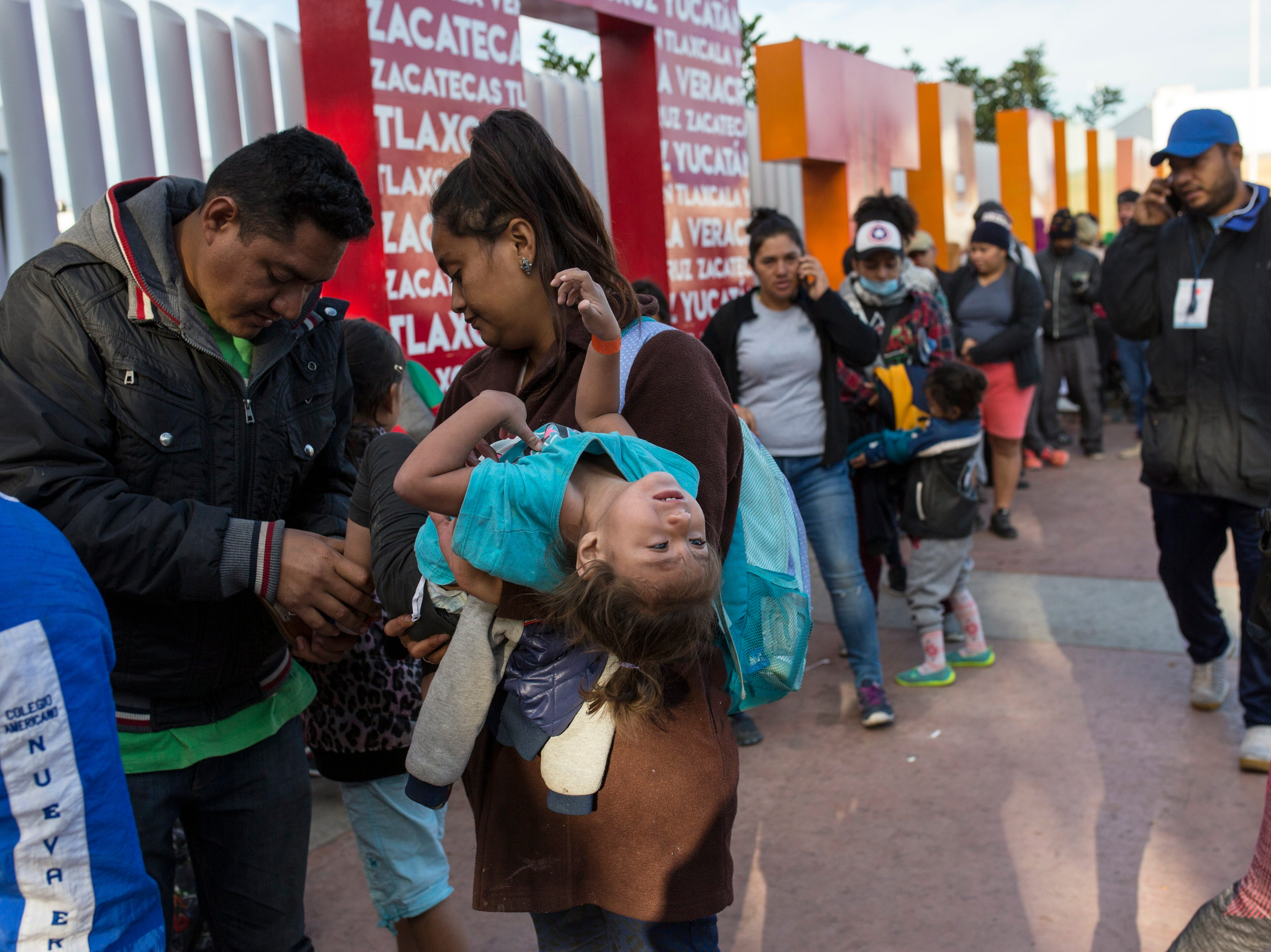 Sairy Hueso, part of the Central American migrant caravan, carries her daughter Etzabe Ponce, as she stands next to her husband while waiting in line to receive a number as part of the process to apply for asylum in the United States, at the border in Tijuana, Mexico Tijuana, Mexico, Friday, Nov. 16, 2018.