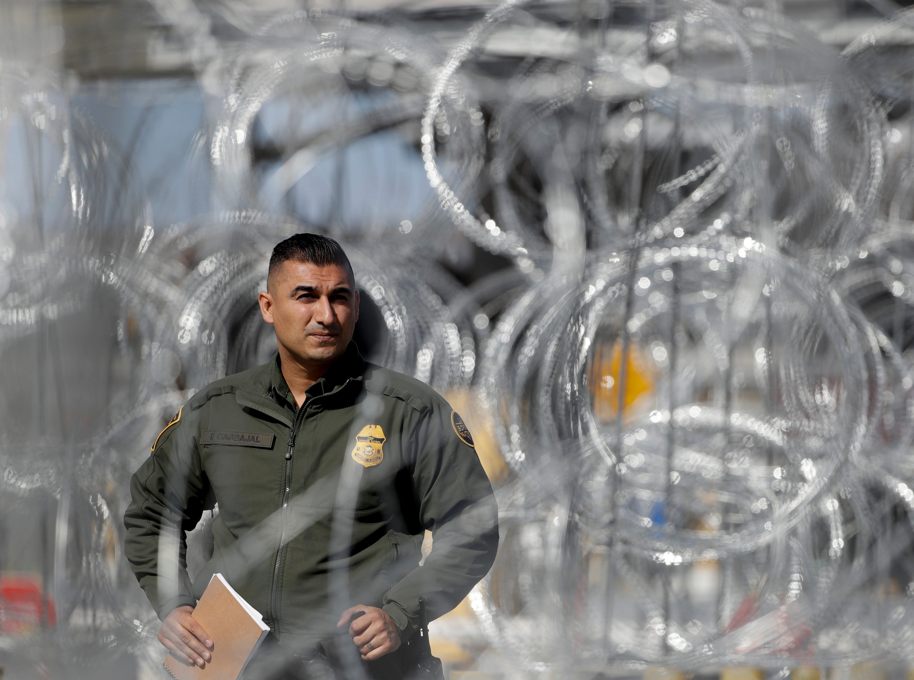 A U.S. Border Patrol agent looks through concertina wire during a tour of the San Ysidro port of entry Friday, Nov. 16, 2018, in San Diego.