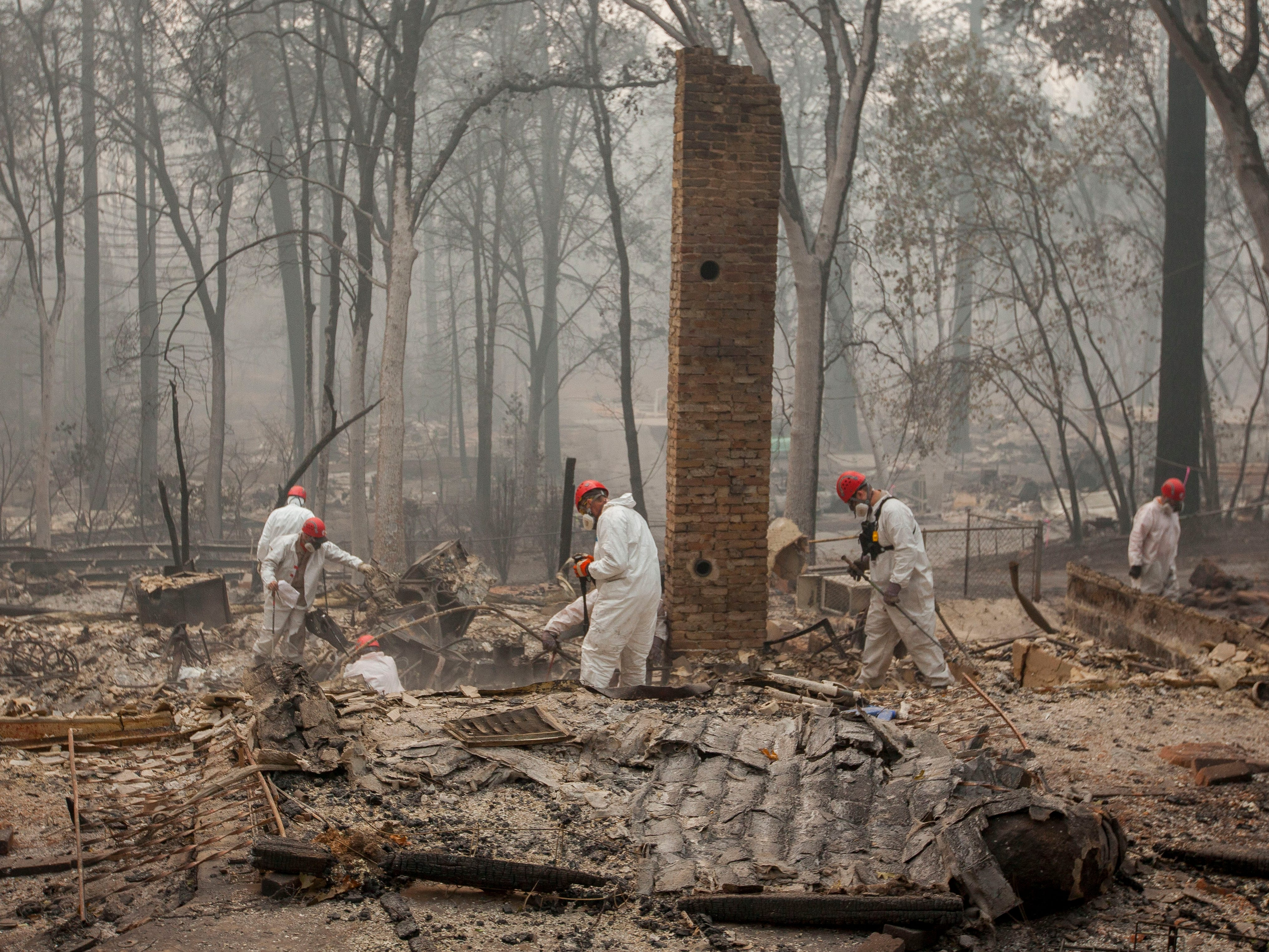 Search and rescue personnel comb through debris searching for remains in a neighborhood near Pentz Road in Paradise, Calif, after the Camp Fire devastated the area, Nov. 15, 2018.