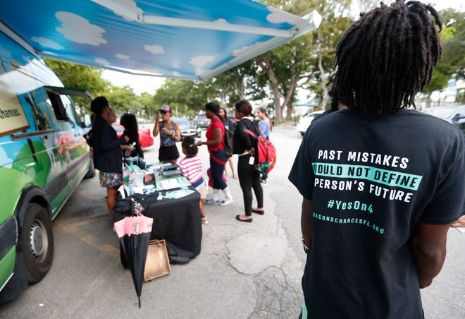 "People gathered around the Ben & Jerry's ""Yes on 4"" truck as they learned about Amendment 4 before the midterm elections and ate free ice cream in Miami. The amendment, which passed on Nov. 6, restores voting rights to ex-felons."