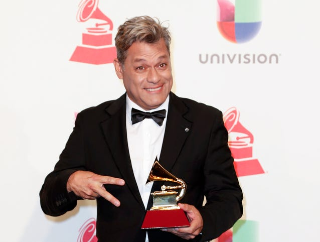 Juan Carlos Luces holds the trophy for Best Tropical Song.