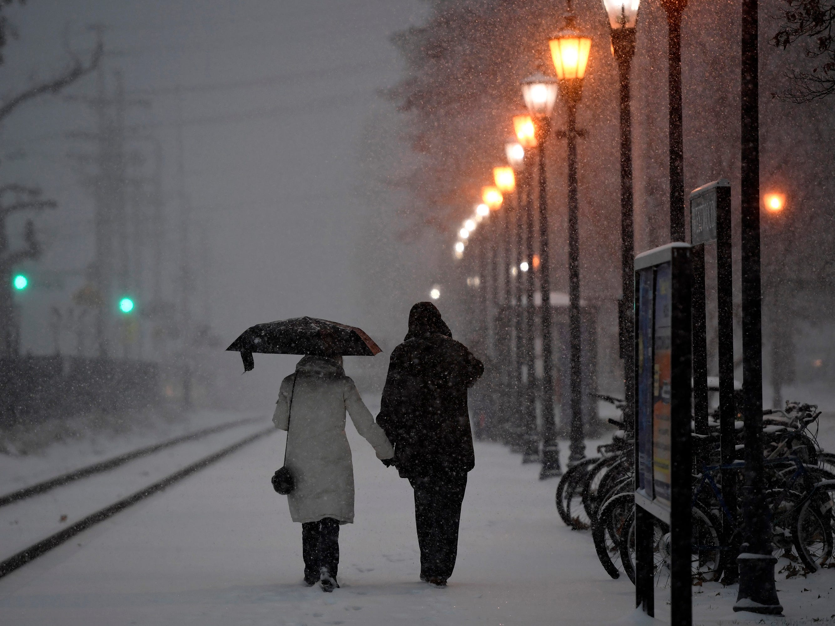 A couple walks along the railroad tracks into the Westwood N.J. Transit train station as the first snowfall of the year hits New Jersey and the Northeast on Nov. 15, 2018.