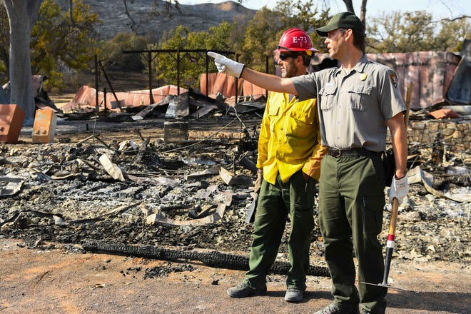 Fire Capt. Ryan O'Neill, left, and the National Park Service's Robert Cromwell look for hot spots at the Paramount Ranch in Agoura Hills on Nov. 16, 2018, a few days after the Woolsey Fire tore through.
