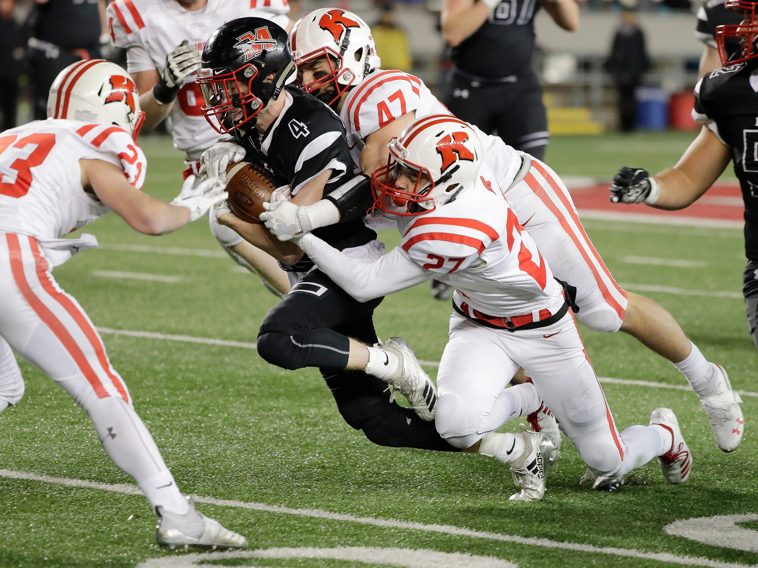 Muskego's RJ Bosshart (4) is tackled by a group of Kimberly players in the WIAA Division 1 championship game at Camp Randall Stadium on Friday, November 16, 2018 in Madison, Wis.