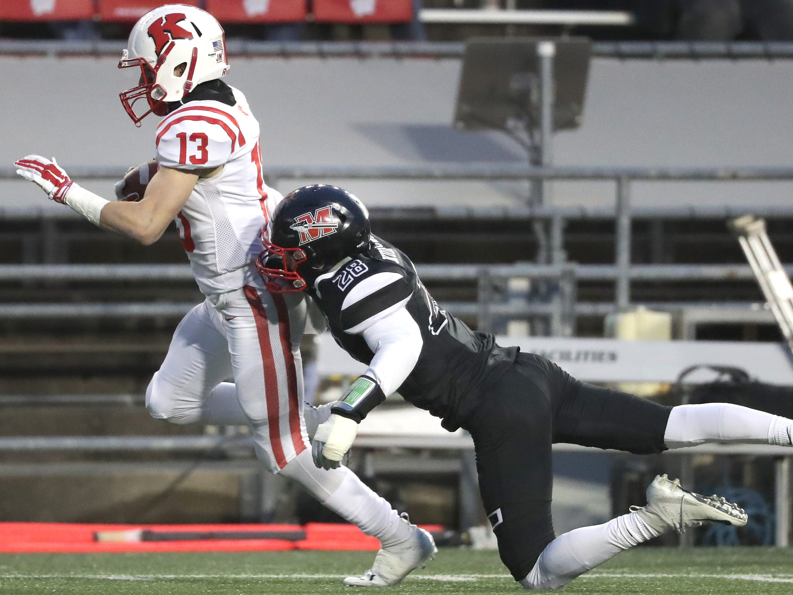 Kimberly High School's #13 Zach Lechnir is chased by Muskego High School's #28 Michael Kudronowicz following a pass reception during the WIAA Division 1 state championship football game on Friday, November 16, 2018, at Camp Randall in Madison, Wis.