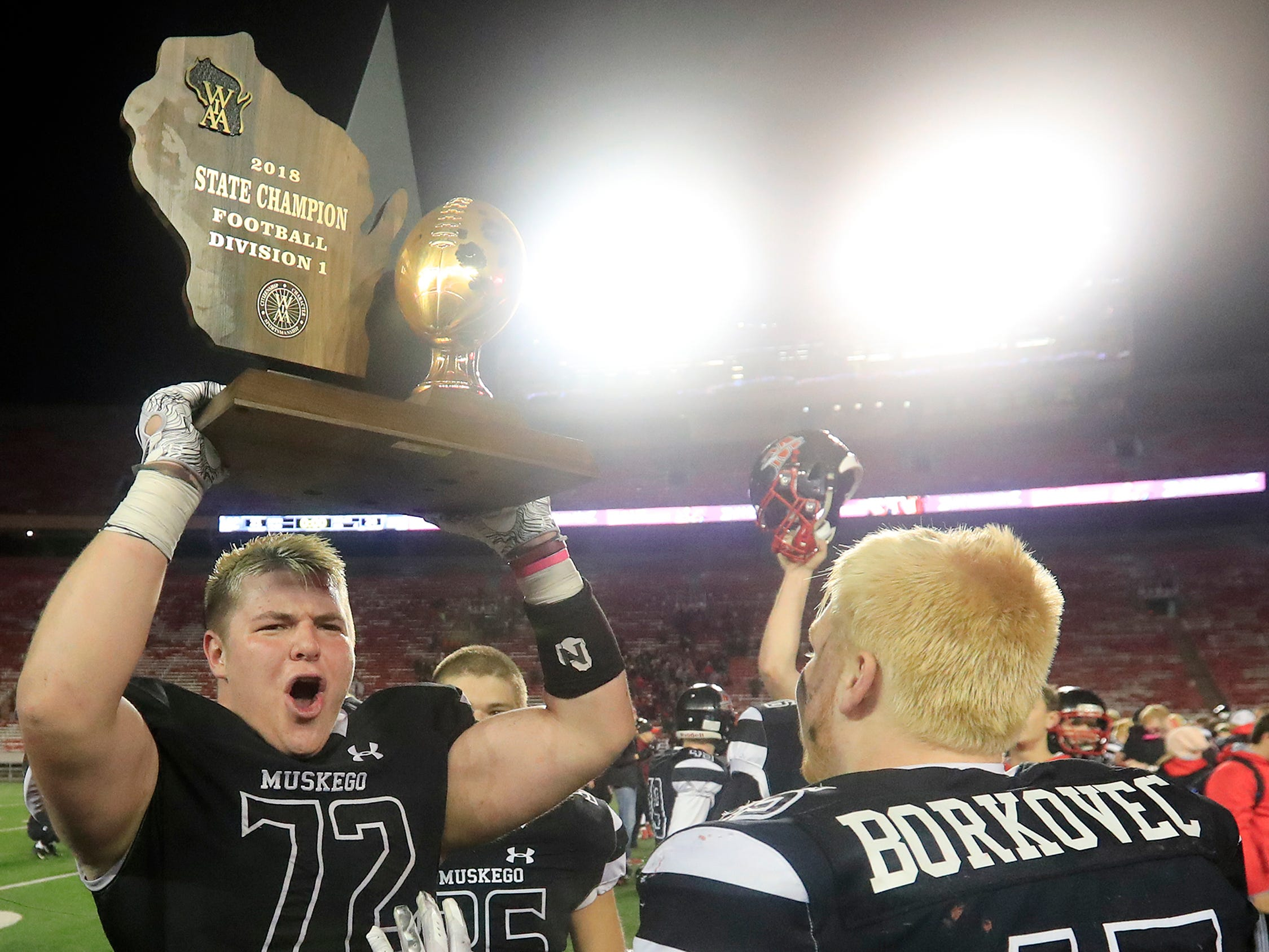 Muskego's Nathaniel Stewart (72) holds up the trophy after the Warriors defeated Kimberly to win the WIAA Division 1 championship game at Camp Randall Stadium on Friday, November 16, 2018 in Madison, Wis.