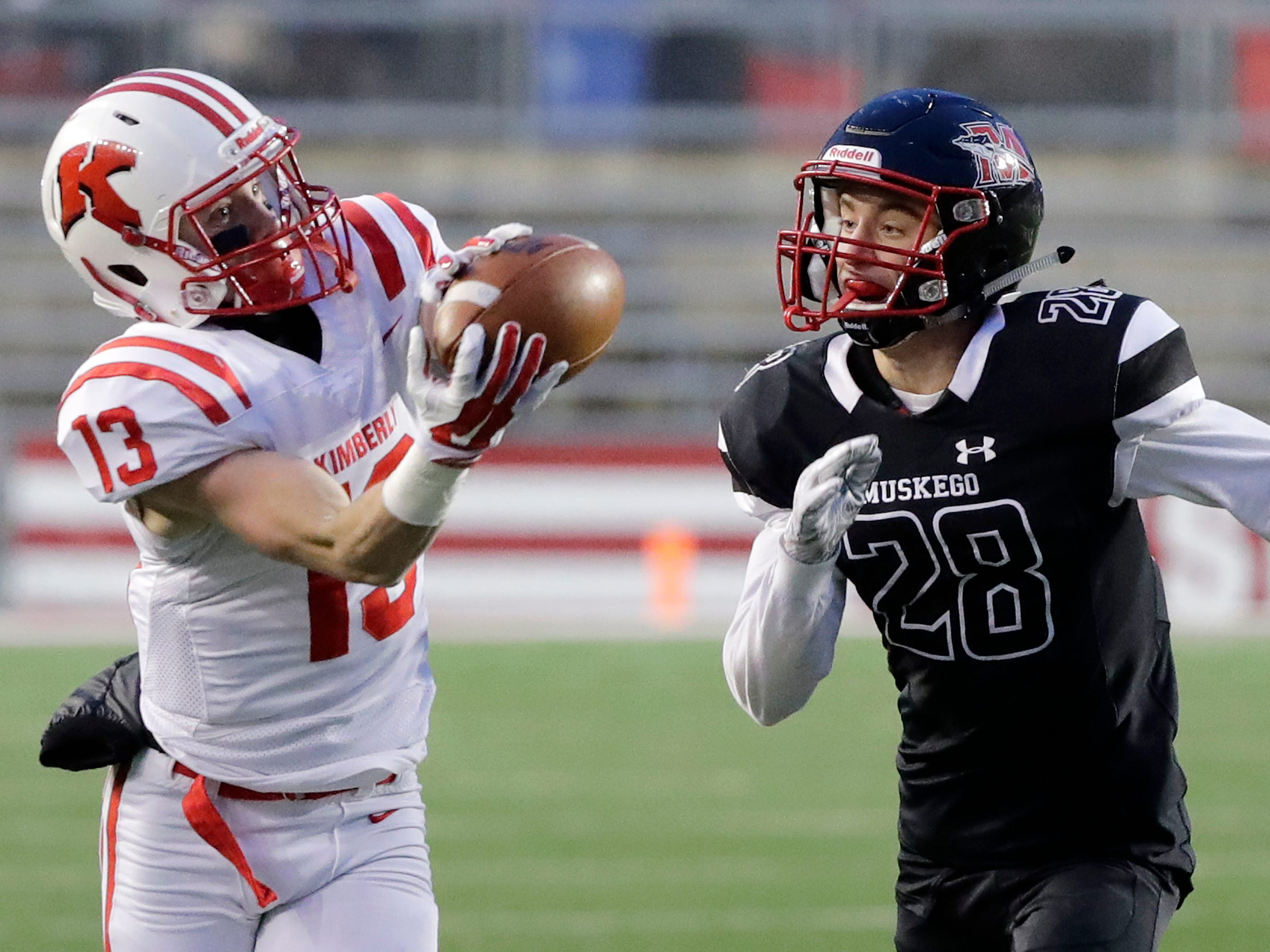 Kimberly's Zach Lechnir (13) catches a pass against the coverage of Muskego's Mitchel Kudronowicz (28) in the WIAA Division 1 championship game at Camp Randall Stadium on Friday, November 16, 2018 in Madison, Wis.