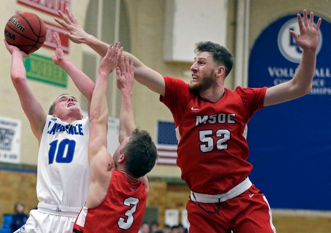 Brad Sendell of Lawrence University goes up for a shot while being defended by Jason Palesse and Dylan Hamlin (52) of  MSOE on Saturday at Alexander Gym in Appleton.
