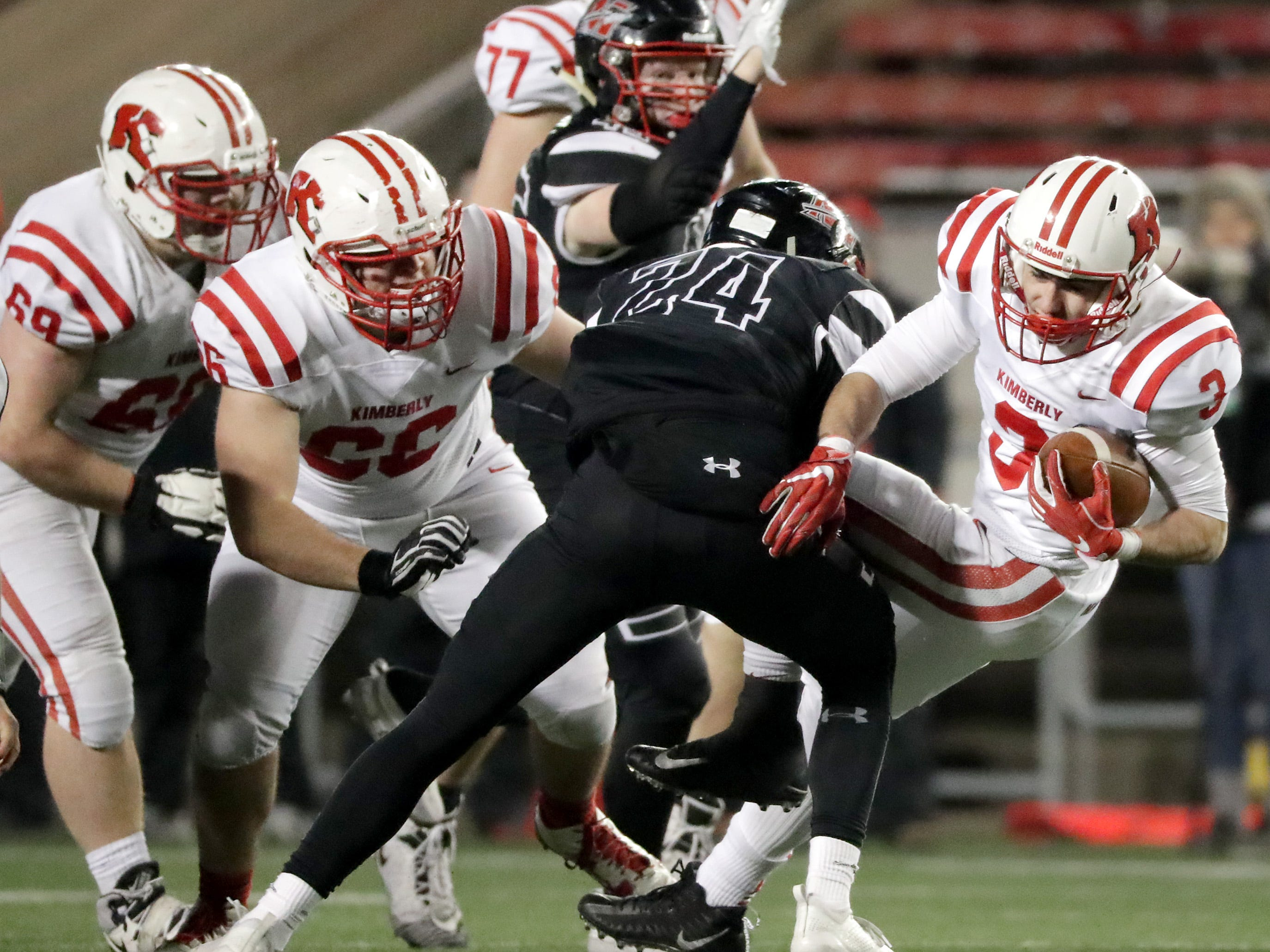 Kimberly High School 's #3 Alec Martzahl is tackled by Muskego High School's #24 Huntyer Wohler during the WIAA Division 1 state championship football game on Friday, November 16, 2018, at Camp Randall in Madison, Wis.