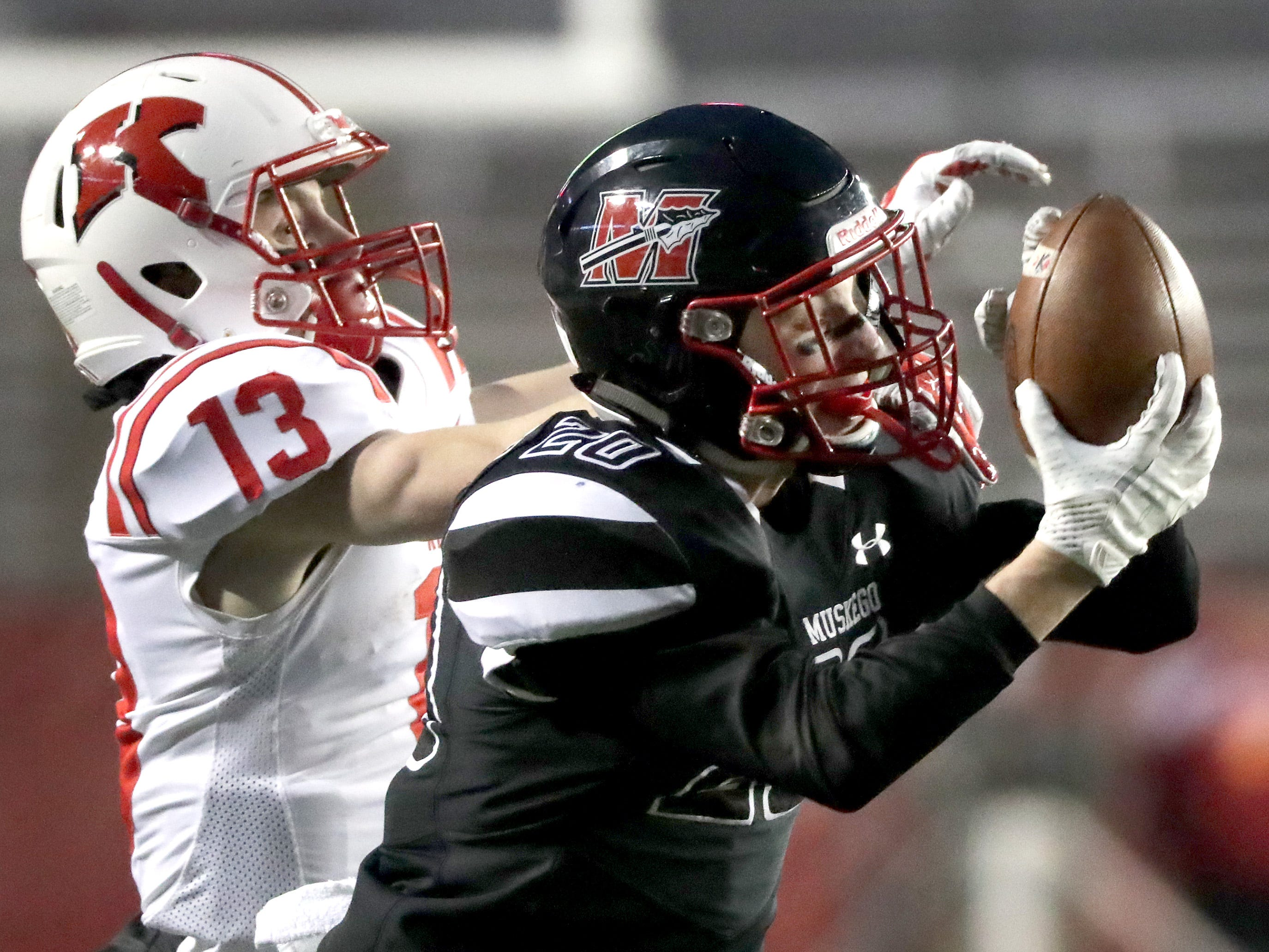Muskego High School's #20 Sam Chovanec intercepts a pass intended for Kimberly High School's #13 Zach Lechnir during the WIAA Division 1 state championship football game on Friday, November 16, 2018, at Camp Randall in Madison, Wis.