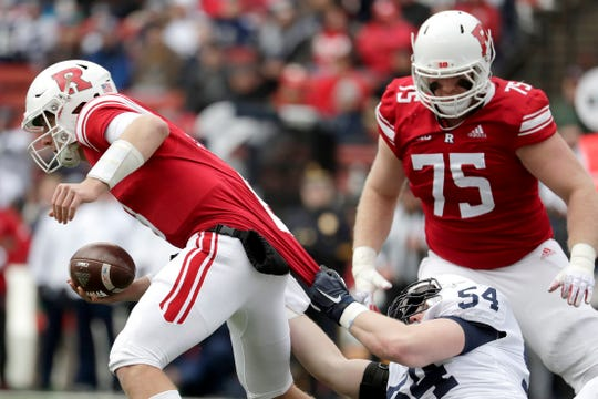 Penn State defensive tackle Robert Windsor, bottom right, grabs at the jersey of Rutgers quarterback Artur Sitkowski, left, while recording a sack in 2018. Rutgers' Zach Venesky (75) looks on during the play.