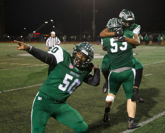 Long Branch players are shown celebrating the NJSIAA Central Group IV championship Friday night after the Green Wave's 21-14 win over Brick.