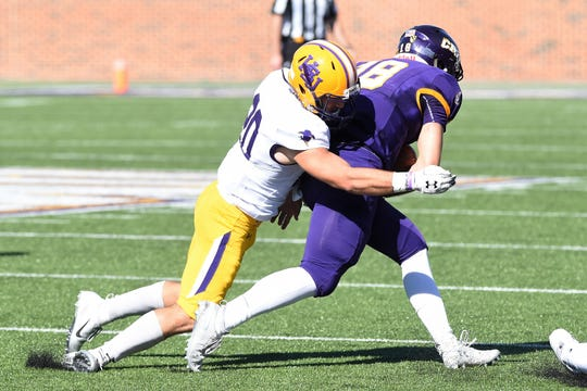 Hardin-Simmons safety Cameron Hanna (20) wraps up Mary Hardin-Baylor quarterback Jase Hammack (18) in the first round of the NCAA Division III playoffs at Crusader Stadium in Belton on Saturday, Nov. 17, 2018.