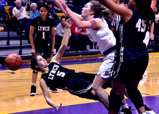 Bishop Lynch's Natalie Lark is knocked down after fouling Wylie's Balley Roberts during the final game of the Polk-Key City Basketball Classic at Hardin-Simmons University.