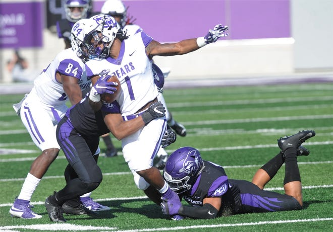 Central Arkansas running back Cedric Battle (1) is tackled by ACU's Qua'Shawn Washington, left, and Jeremiah Chambers after a catch in the first quarter.