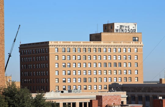 After Abilene Fire Department ladders reached up into the downtown Abilene skyline Thursday, a crane was called into service Friday to remove pests from the Windsor.