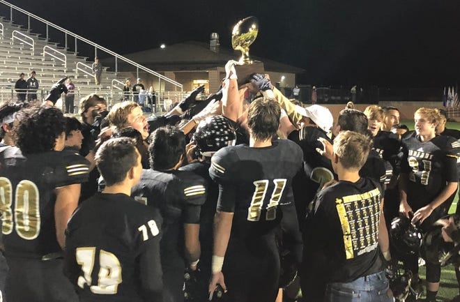 The Comanche football team raises the Region II-3A Division II bi-district trophy following Friday's 42-30 win against Nocona in Mineral Wells.