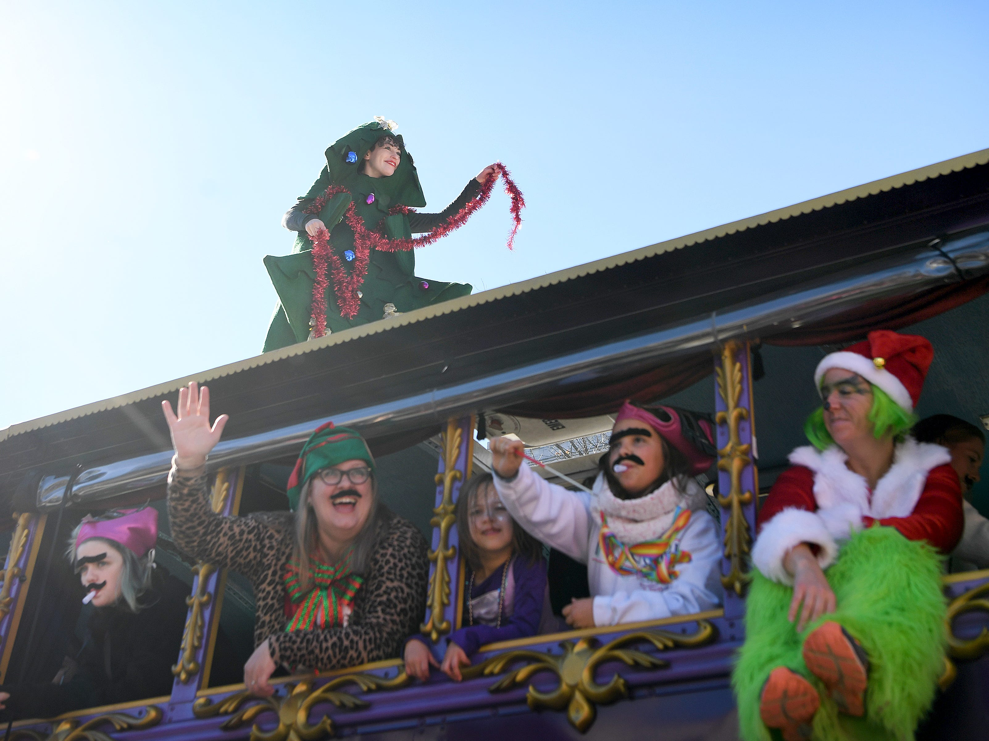 Paraders aboard the LaZoom bus wave to the crowd during the 2018 Asheville Holiday Parade on Nov. 17, 2018. More than 100 entries walked through the streets lined with spectators in the parade this year.