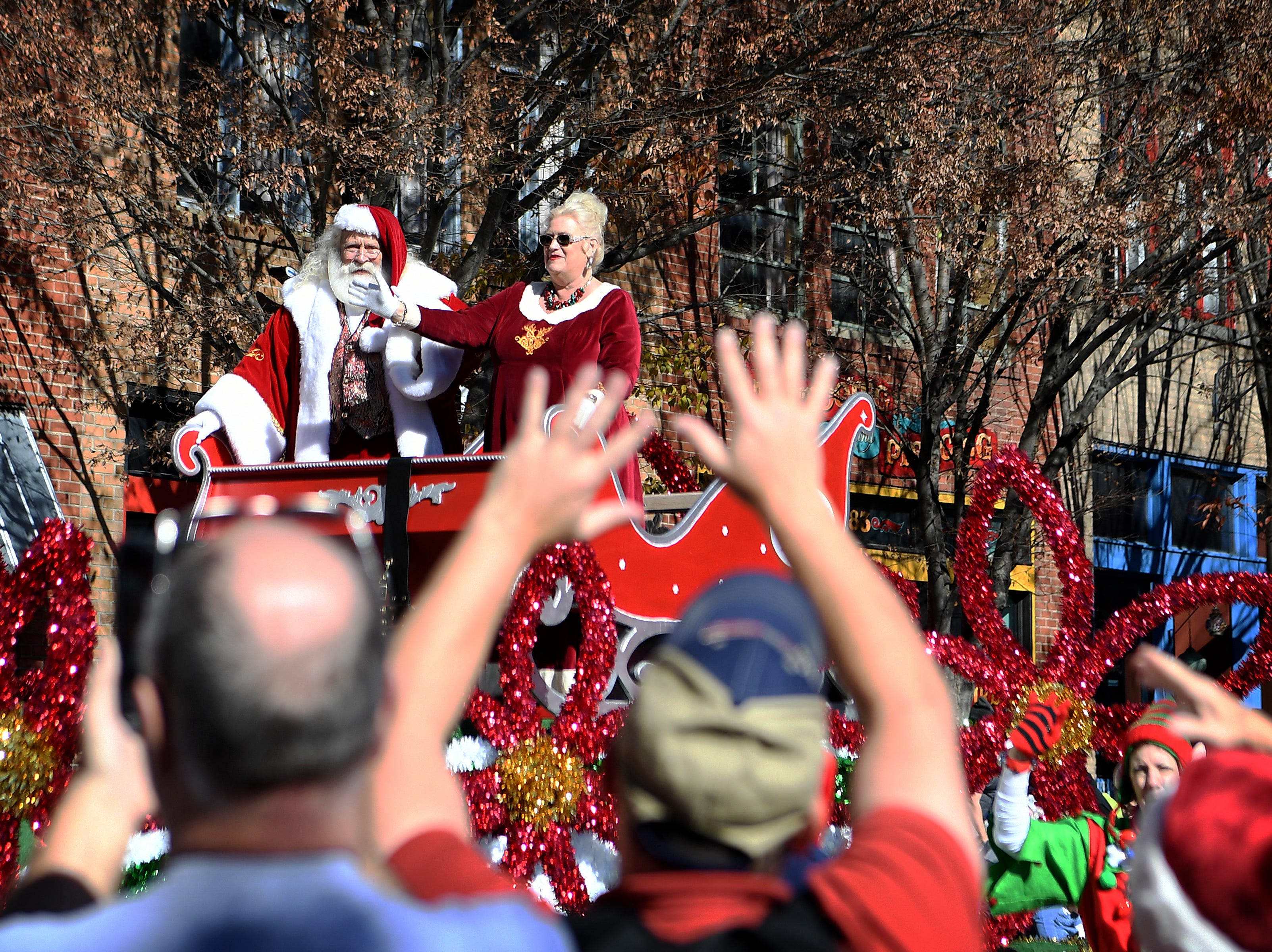 Santa and Mrs. Claus aboard the North Carolina Arboretum Winter Lights float make their way down Patton Avenue to close out the 2018 Asheville Holiday Parade on Nov. 17, 2018. More than 100 entries walked through the streets lined with spectators in the parade this year.