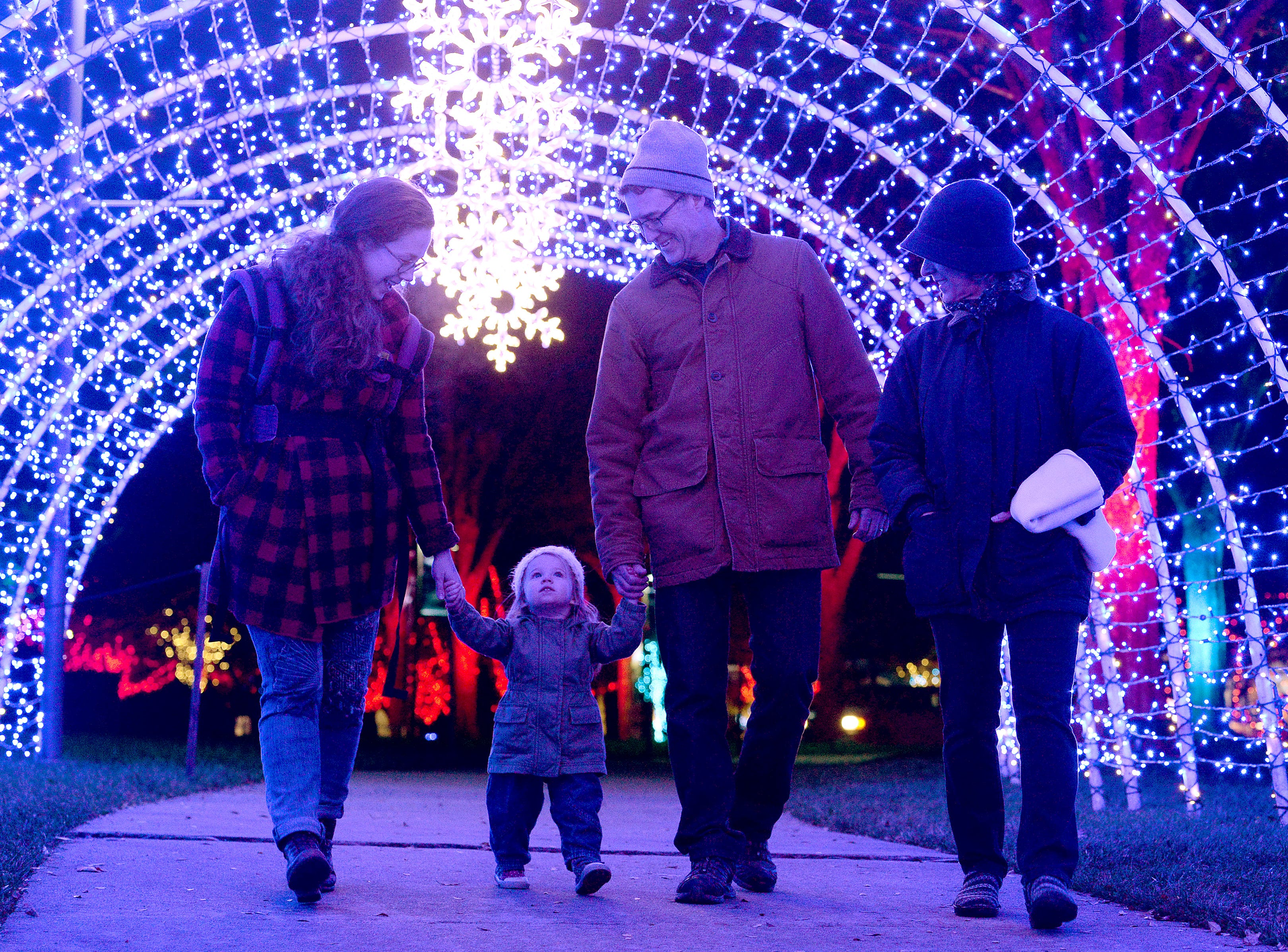 River Oliver, 18 months, walks through a tunnel of lights with her mother, Jacqueline and grandparents, Patrick and Gale McNally during the Winter Lights show at the North Carolina Arboretum on Nov. 16, 2018. The show runs nightly through the end of the year.
