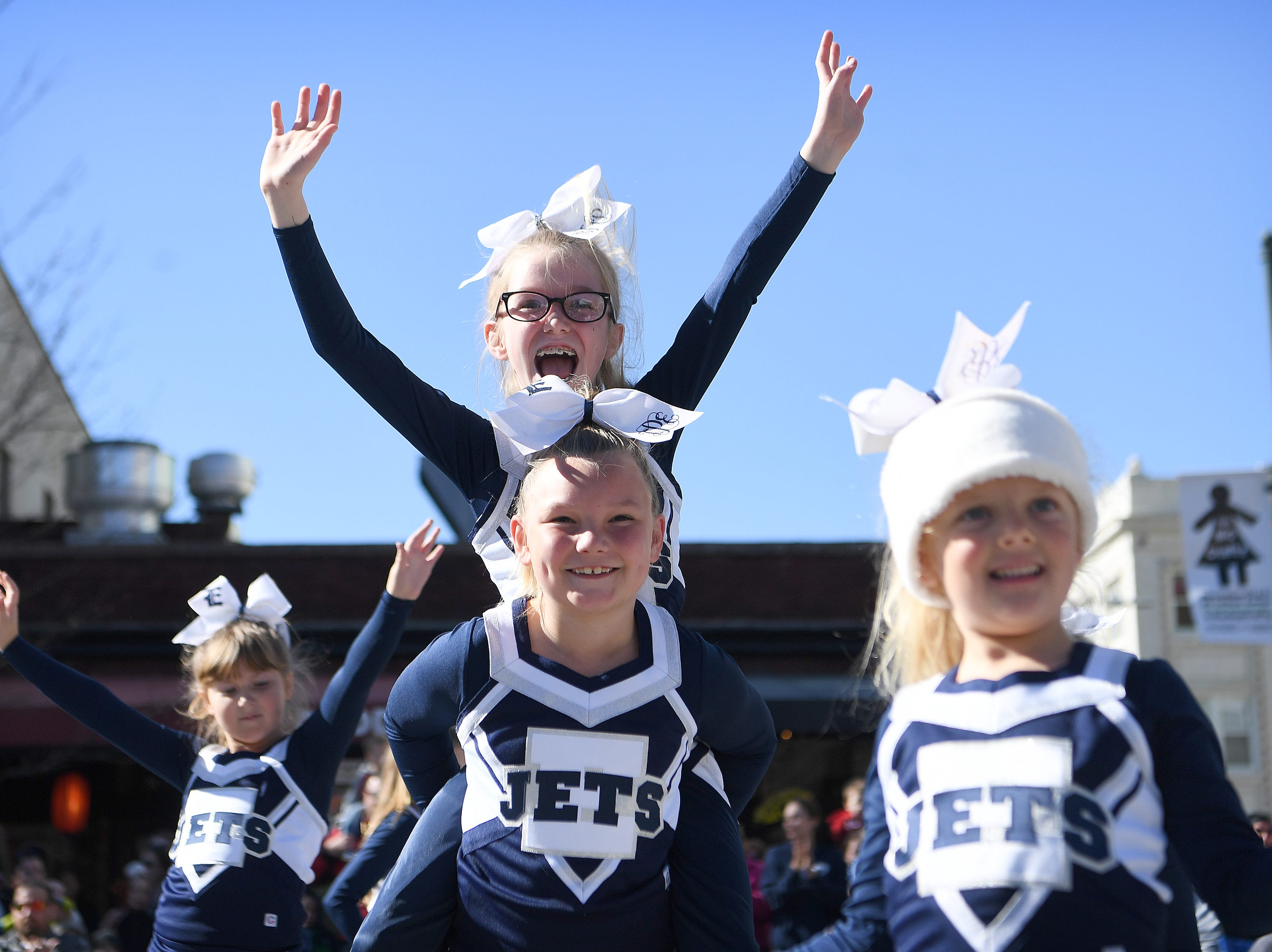 Hominy Valley Youth Cheerleaders strike an ending pose after performing for the judges at the corner of Biltmore and Patton Avenues during the 2018 Asheville Holiday Parade on Nov. 17, 2018. More than 100 entries walked through the streets lined with spectators in the parade this year.