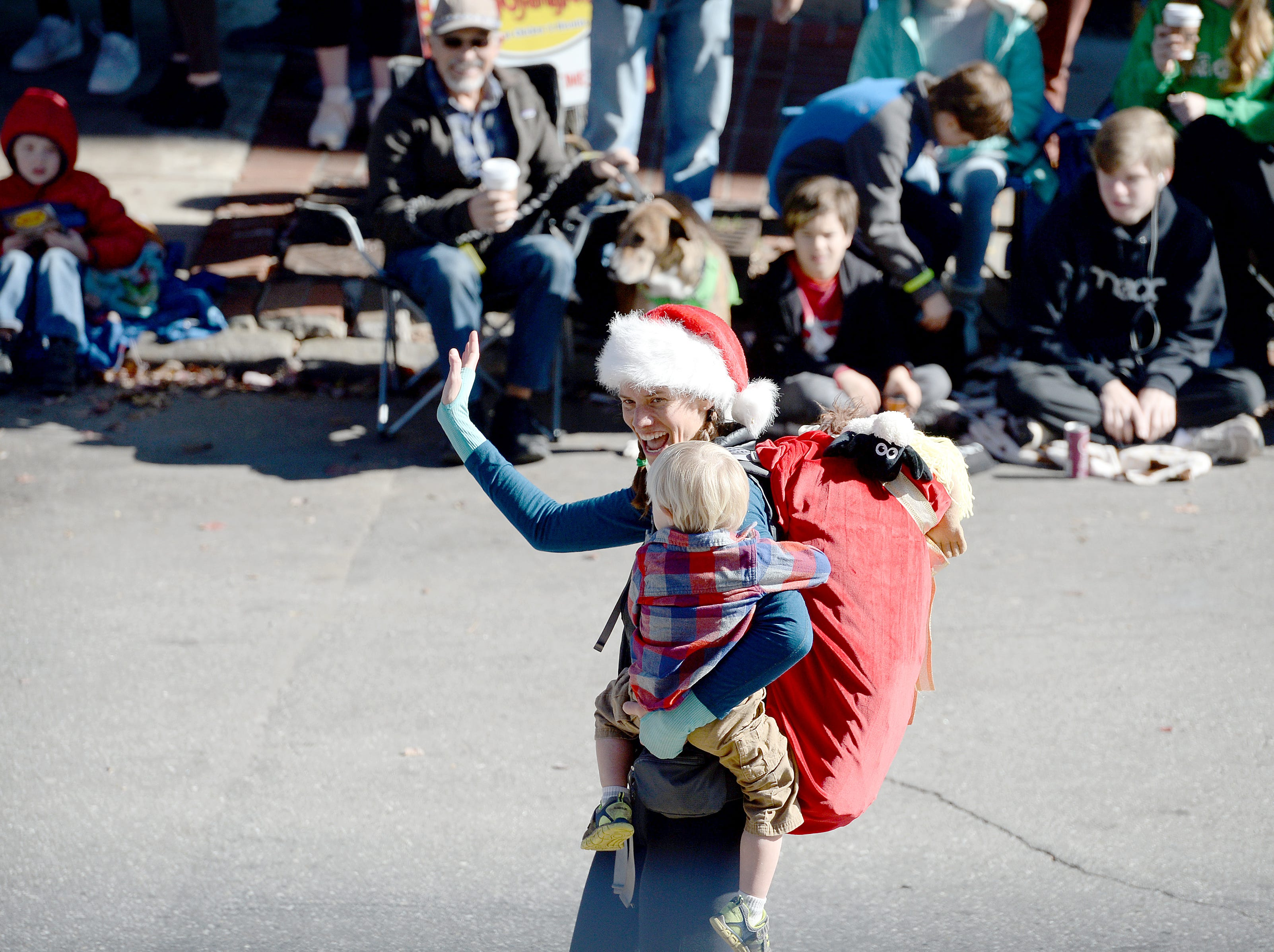 Jennifer Pharr Davis, Grand Marshal of the 2018 Asheville Holiday Parade, hikes her way up Biltmore Avenue on Nov. 17, 2018. More than 100 entries walked through the streets lined with spectators in the parade this year.