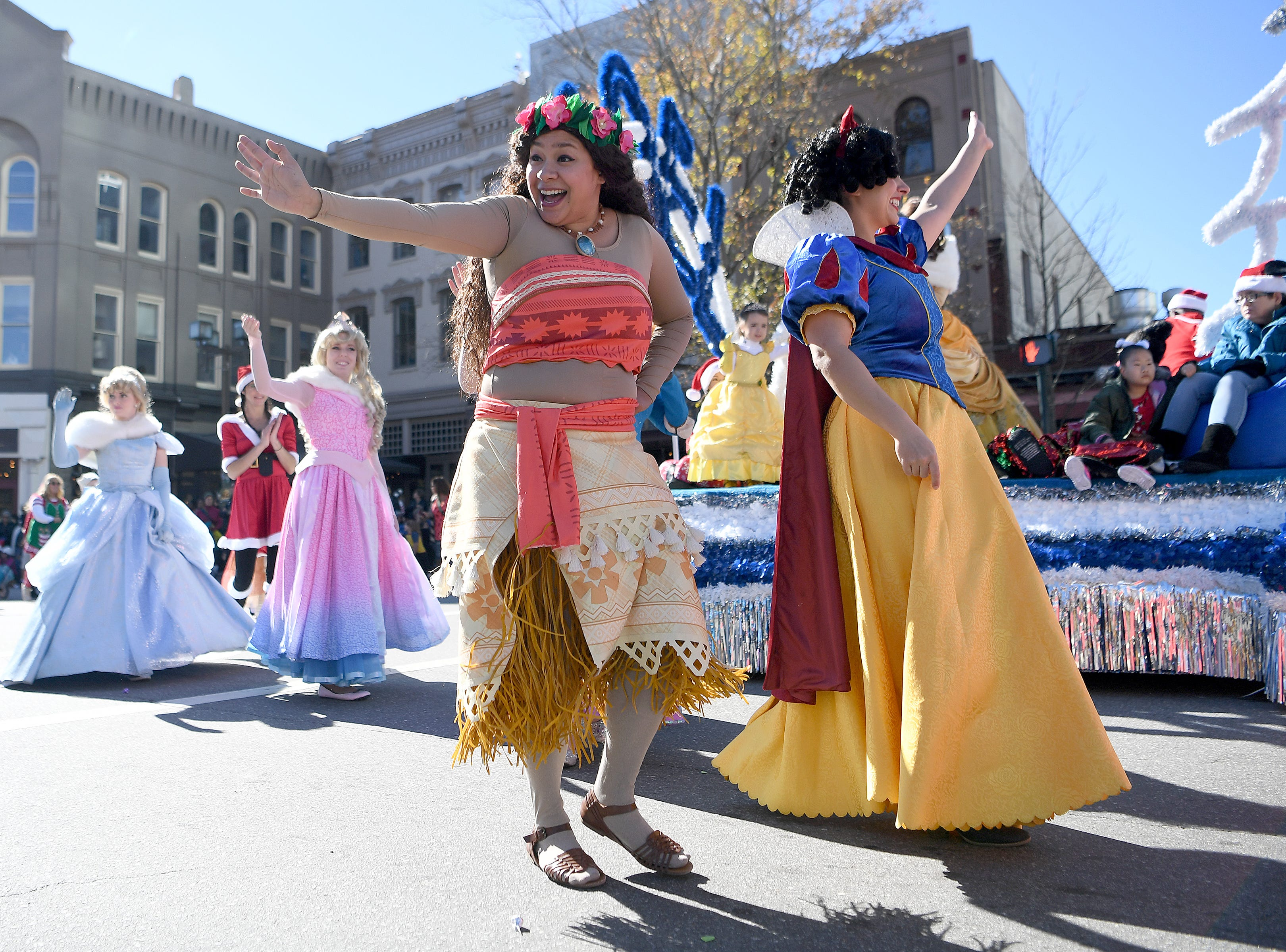 Women dressed as princesses with Songs Sealed Delivered party entertainment wave to the crowd before they perform for the judges at the corner of Biltmore and Patton Avenues during the 2018 Asheville Holiday Parade on Nov. 17, 2018. More than 100 entries walked through the streets lined with spectators in the parade this year.