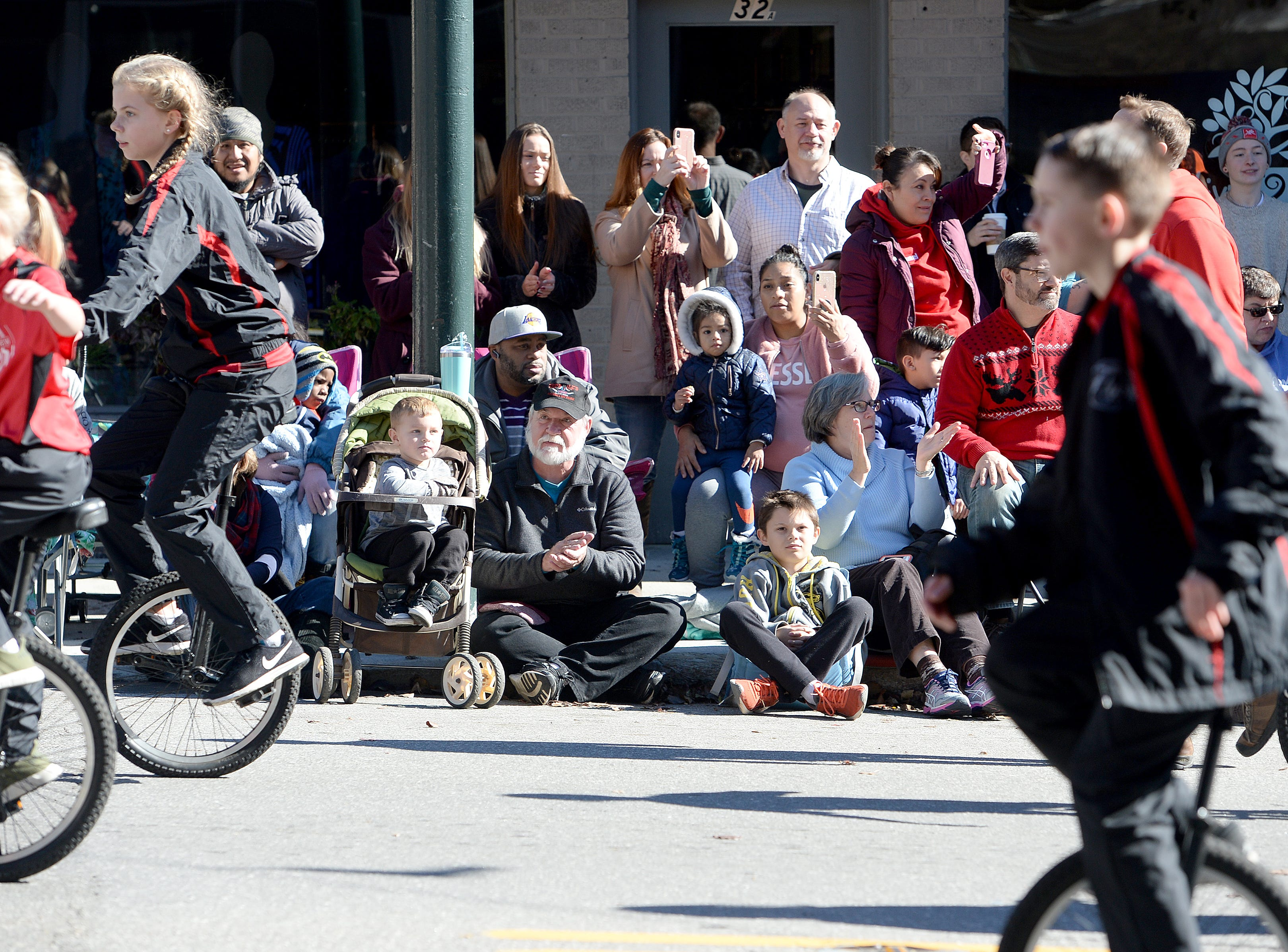 Spectators watch as the Fairview Flyers Unicycle team makes their way up Biltmore Avenue during the 2018 Asheville Holiday Parade on Nov. 17, 2018. More than 100 entries walked through the streets lined with spectators in the parade this year.