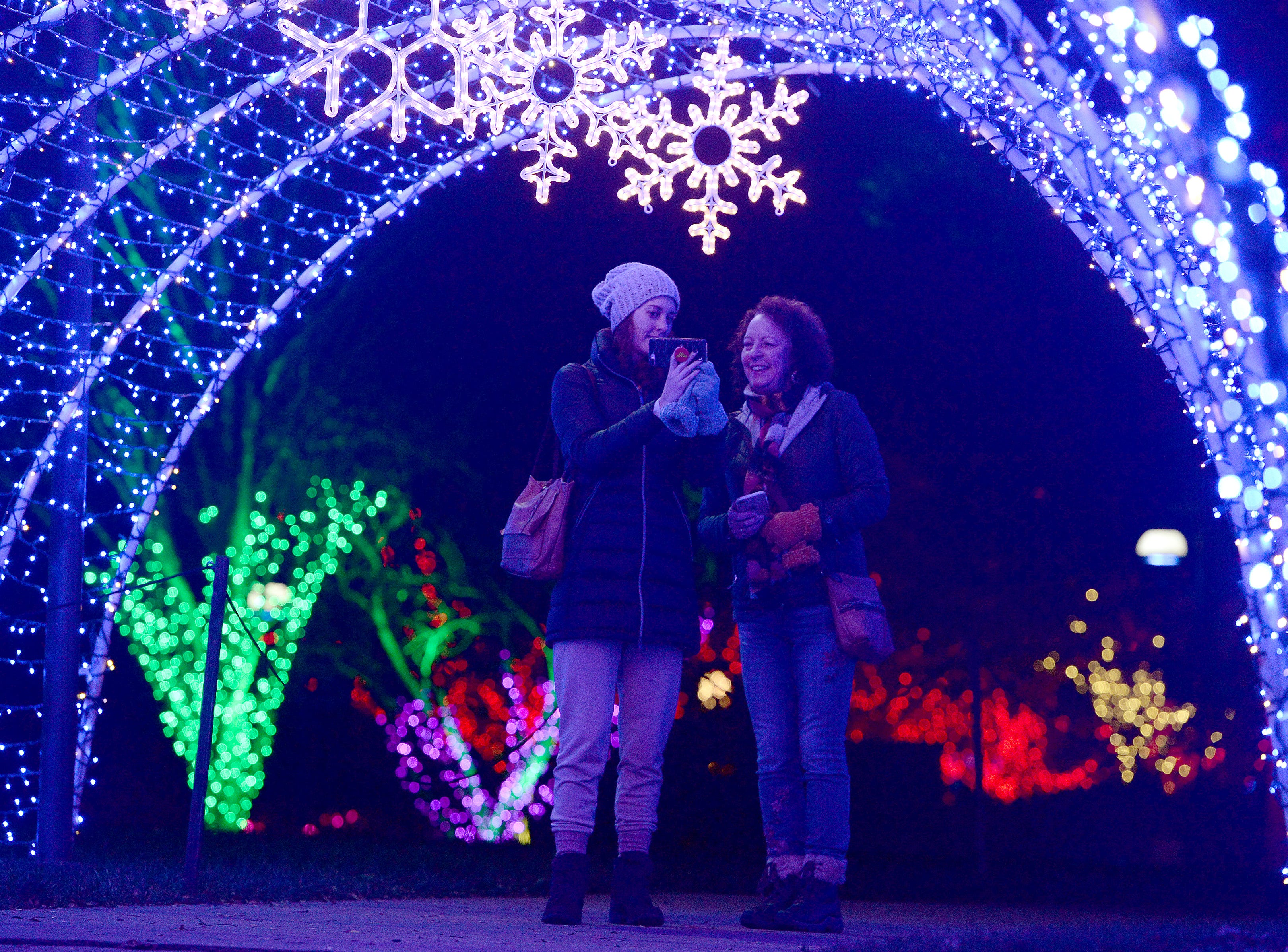 Jessica Ratliff Hicks, left, and her mother, Sharon Ratliff, of Rocky Mount, and Bristol, Tenn. respectively, look at Hicks' phone as they walk through a tunnel of lights during the Winter Lights show at the North Carolina Arboretum on Nov. 16, 2018. The show runs nightly through the end of the year.