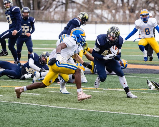 Billy Sheridan of SV sweeps around the left side of the live and comes head to head with Pierre Brown of Cleveland Hill on the way to victory in the New York State Class C Football Semi Finals game.