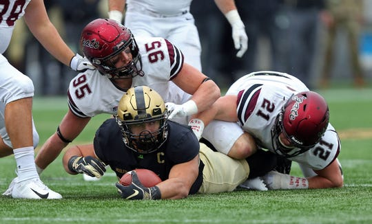 Nov 17, 2018; West Point, NY, USA; Army Black Knights running back Darnell Woolfolk (33) looks up after being tackled on a run by Colgate Raiders linebacker John Steffen (95) and linebacker T.J. Holl (21) during the first half at Michie Stadium. Mandatory Credit: Danny Wild-USA TODAY Sports