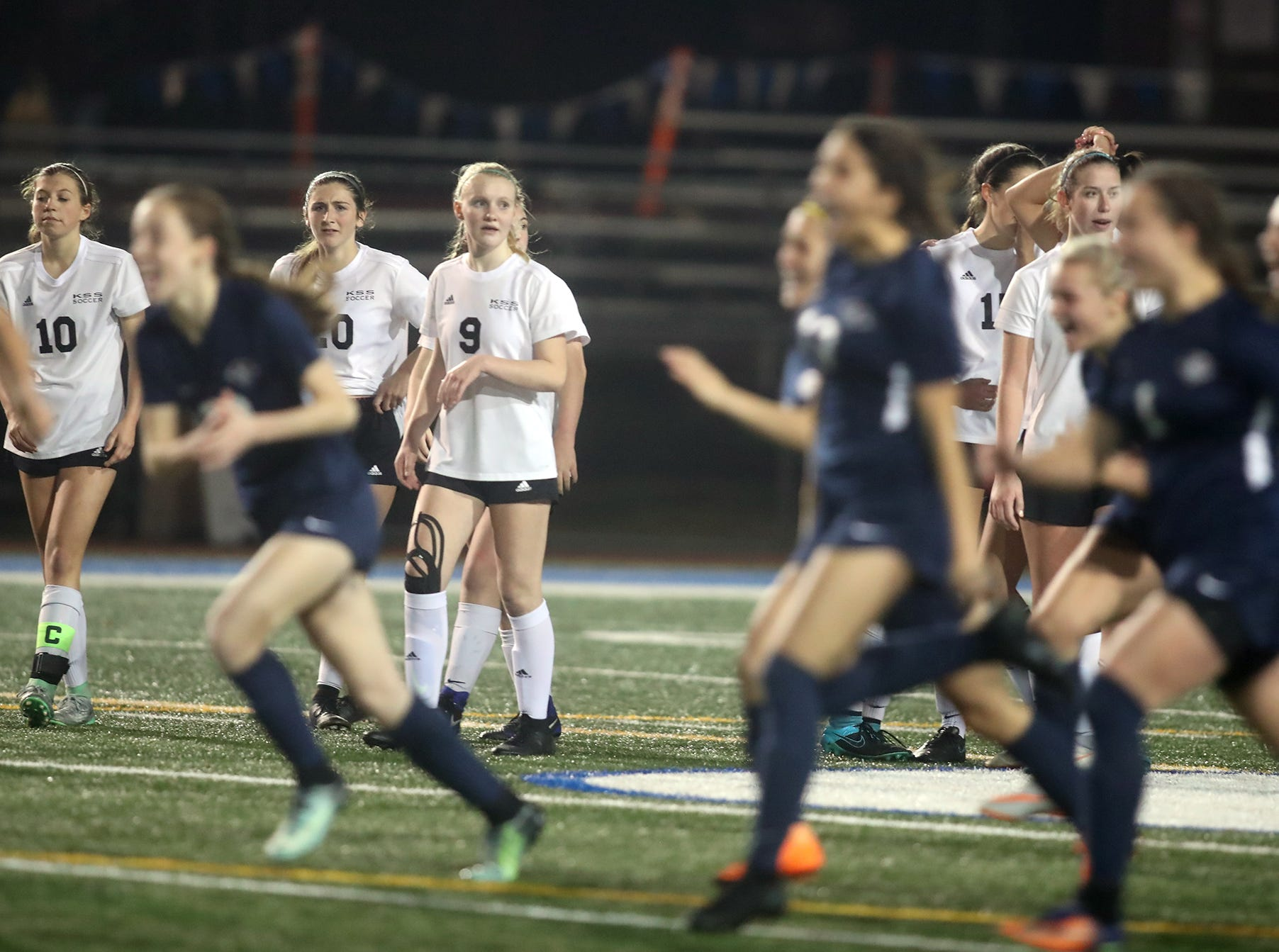The Klahowya girls soccer penalty kickers react as the  KingÕs Way team rushes the field after losing on penalty kicks in overtime in the 2018 Girls Soccer State Championship 1A semifinal game at Shoreline Stadium on Friday, November 16, 2018.