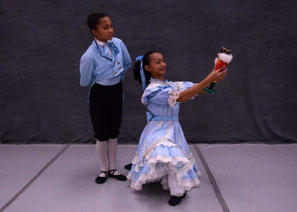 "Clara (Hana Mai Elopre-Thesenga, right) and Franz (Myka Renon) admire Clara's gift in Dance Arts Theatre's production of ""The Nutcracker."""