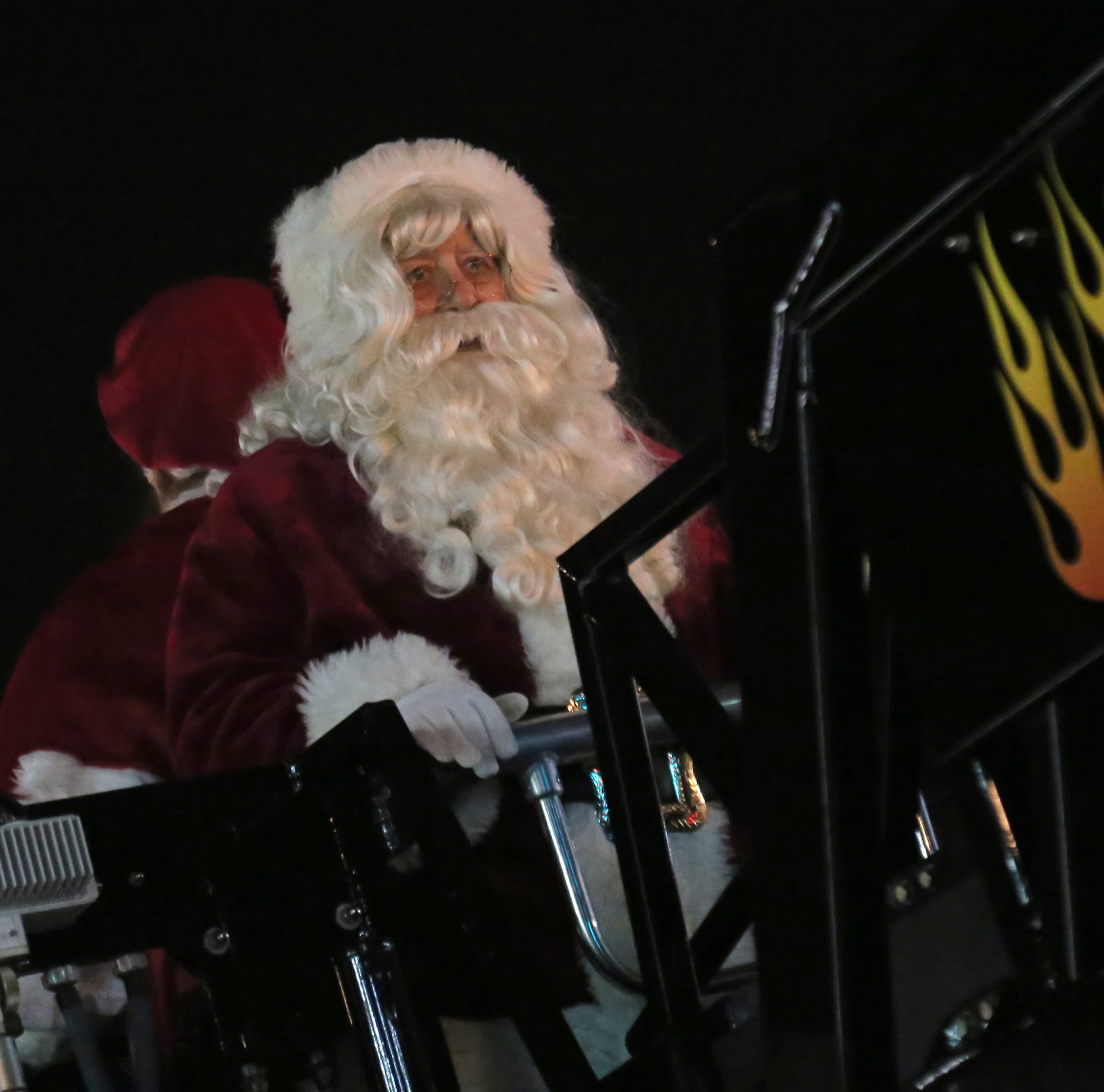 Santa Claus rides into town on the back of a Bucyrus Fire Department ladder truck during the annual Christmas parade on Friday.
