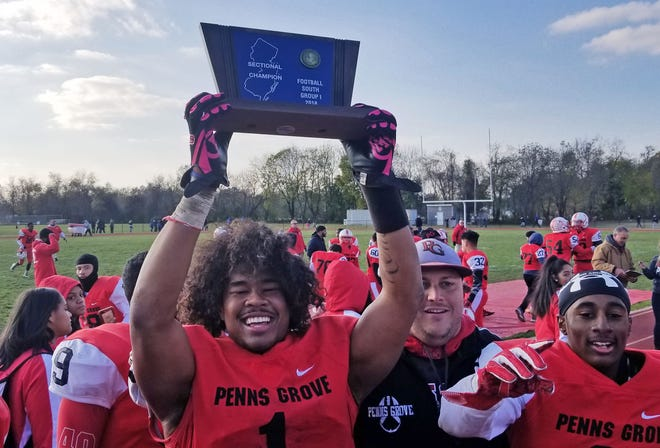 Penns Grove senior Tyreke Brown hoists the South Jersey Group 1 trophy alongside coach John Emel and teammate Jamar Johnson after a 14-7 win over Salem on Saturday.