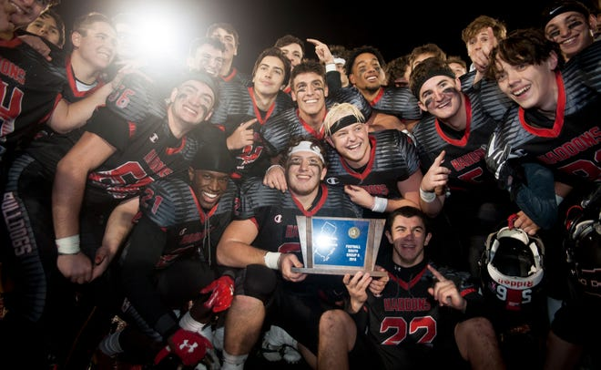 Members of the Haddonfield High School football team gather around their trophy as they celebrate a 23-12 win over Camden South Jersey Group 2 football championship game. The Haddons are the Courier Post Team of the Year.