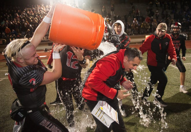 Haddonfield High School's football coach Frank DeLano is doused with water by Haddonfield players Jay Foley, left, and Jack Narducci as they celebrate Haddonfield's 23-12 win over Camden High School in the South Jersey Group 2 football championship game played at Haddonfield High School on Friday, November 16, 2018.