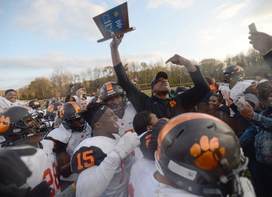 Woodrow Wilson coach Preston Brown hoists the South Jersey Group 3 sectional championship trophy after his Tigers defeated Burlington Township 22-14 at Burlington Township High School, Saturday, Nov. 17, 2018.
