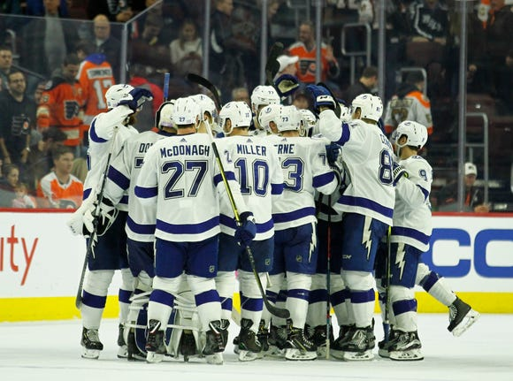 The Tampa Bay Lightning celebrate their overtime win after the Flyers had scored four goals in the final 10 minutes to tie the game.