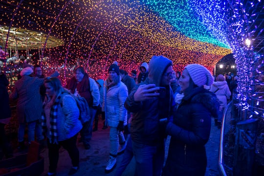 Guests stop to pose for photos in the rainbow tunnel at the 36th annual Festival of Lights at the Cincinnati Zoo on Friday.