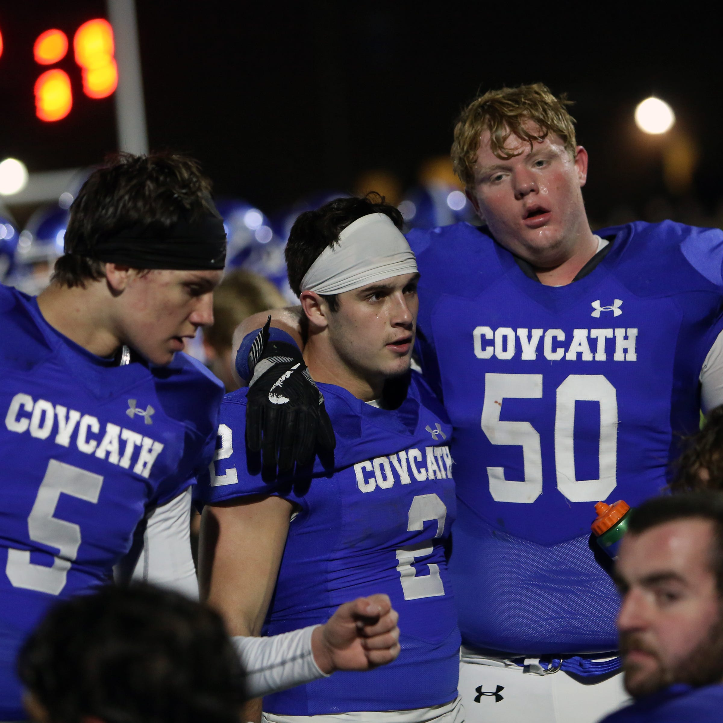 Covington Catholic running back Casey McGinness [2] quarterback Caleb Jacob [5] and center Carter Black meet on the sideline after a touchdown by McGinness. Covington Catholic defeated Highlands 36-0.