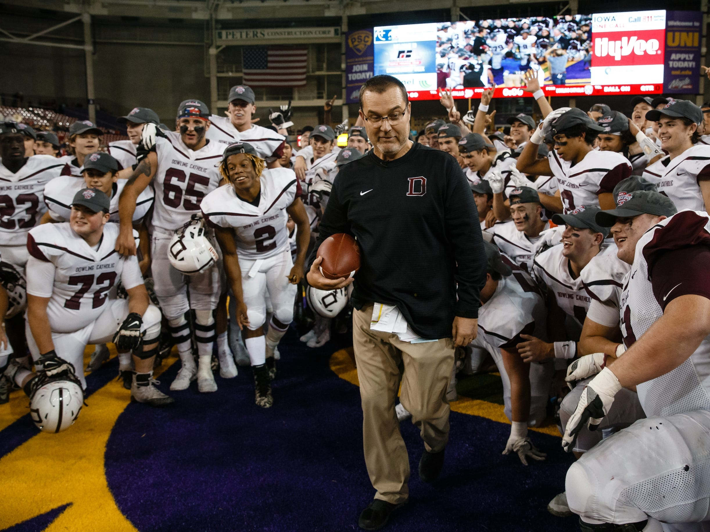 Dowling Catholic head coach Tom Wilson gets out of the way as his players jump to get their state championship trophy after defeating Cedar Falls 22-16 on Friday, Nov. 16, 2018, in Cedar Falls.