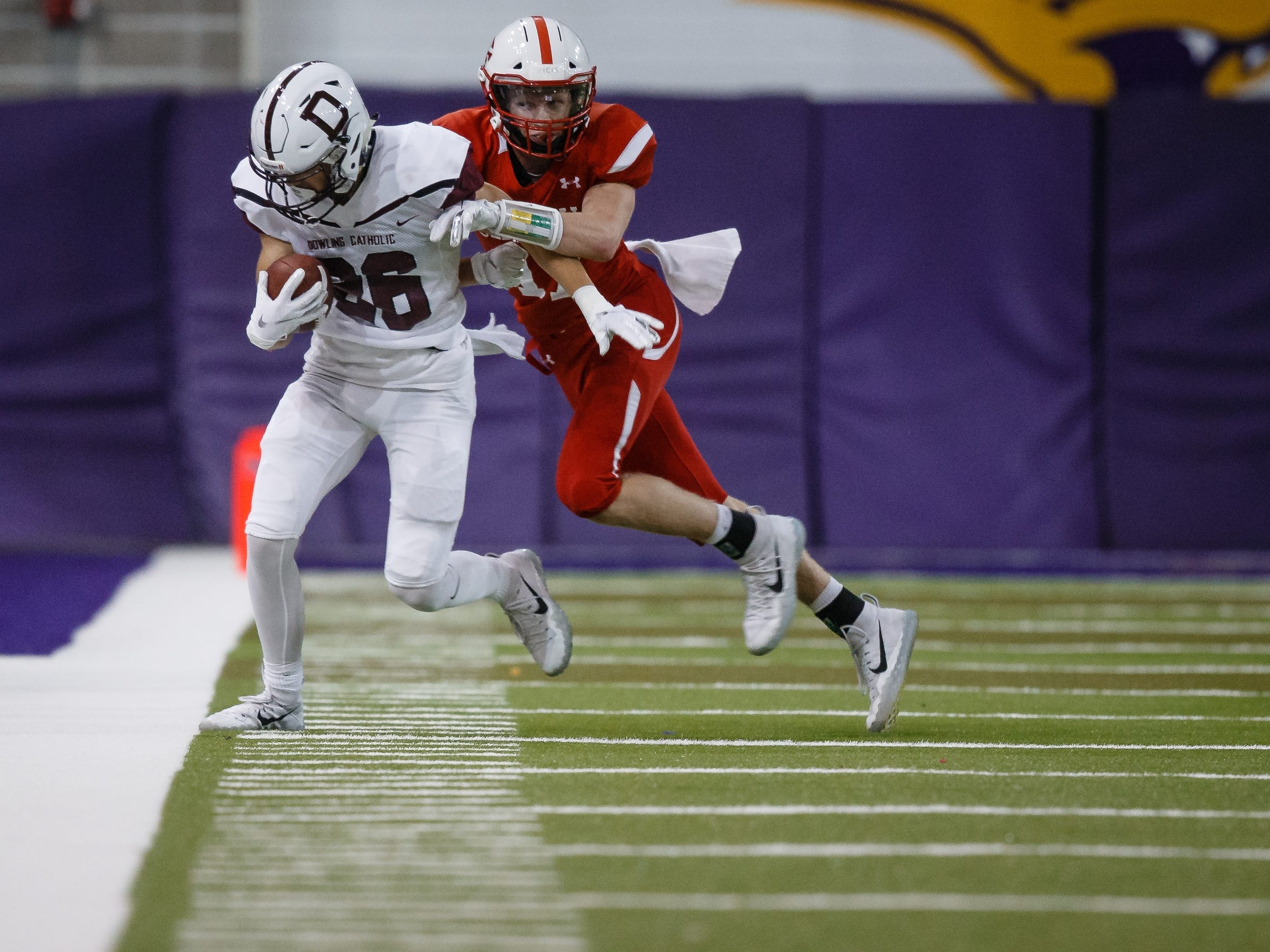 Dowling Catholic's Connor Ibach (26) is pushed out of bounds by Cedar Falls's Logan Wolf (17) during their class 4A state championship football game on Friday, Nov. 16, 2018, in Cedar Falls. Cedar Falls takes a 13-7 lead into halftime.