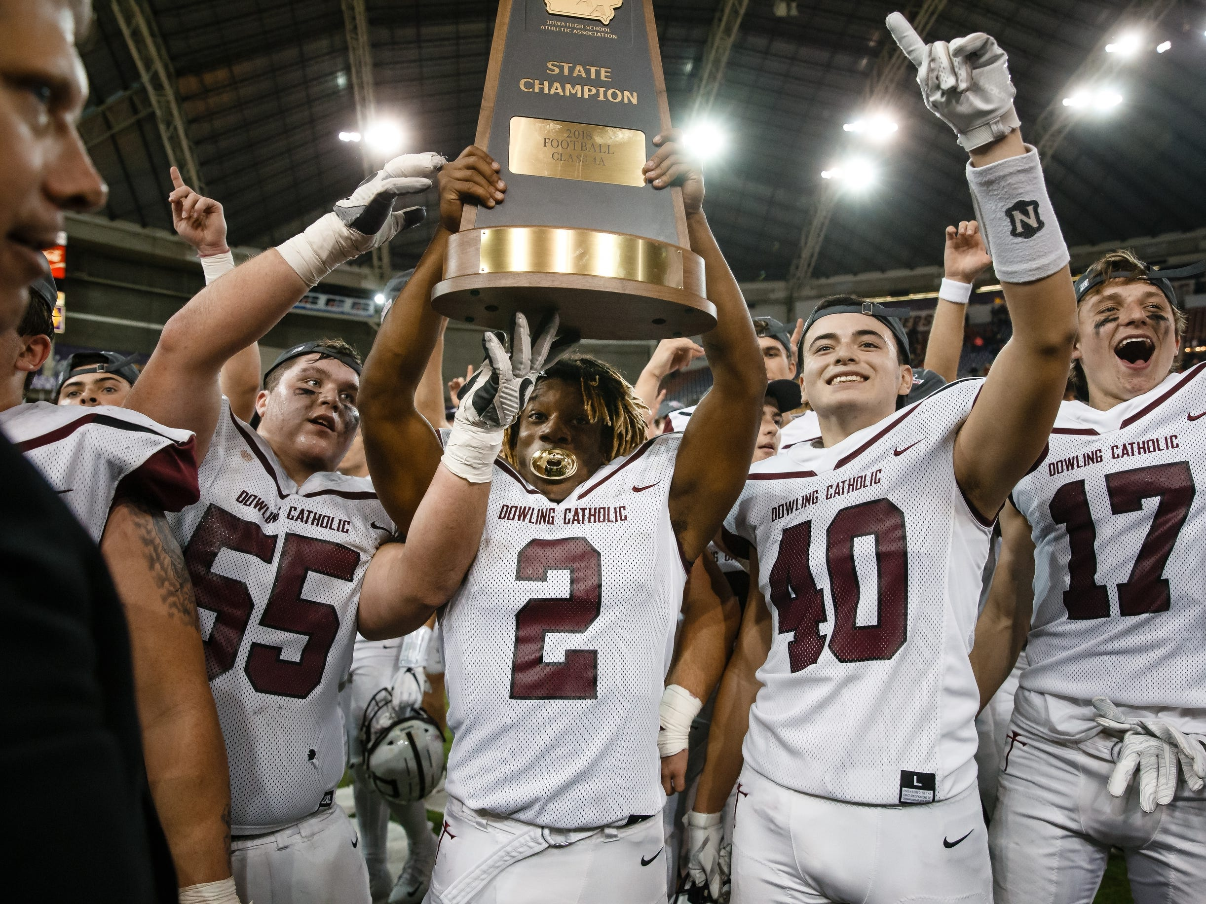 Dowling Catholic celebrates its 22-16 victory over Cedar Falls to win the class 4A state championship football game on Friday, Nov. 16, 2018, in Cedar Falls.