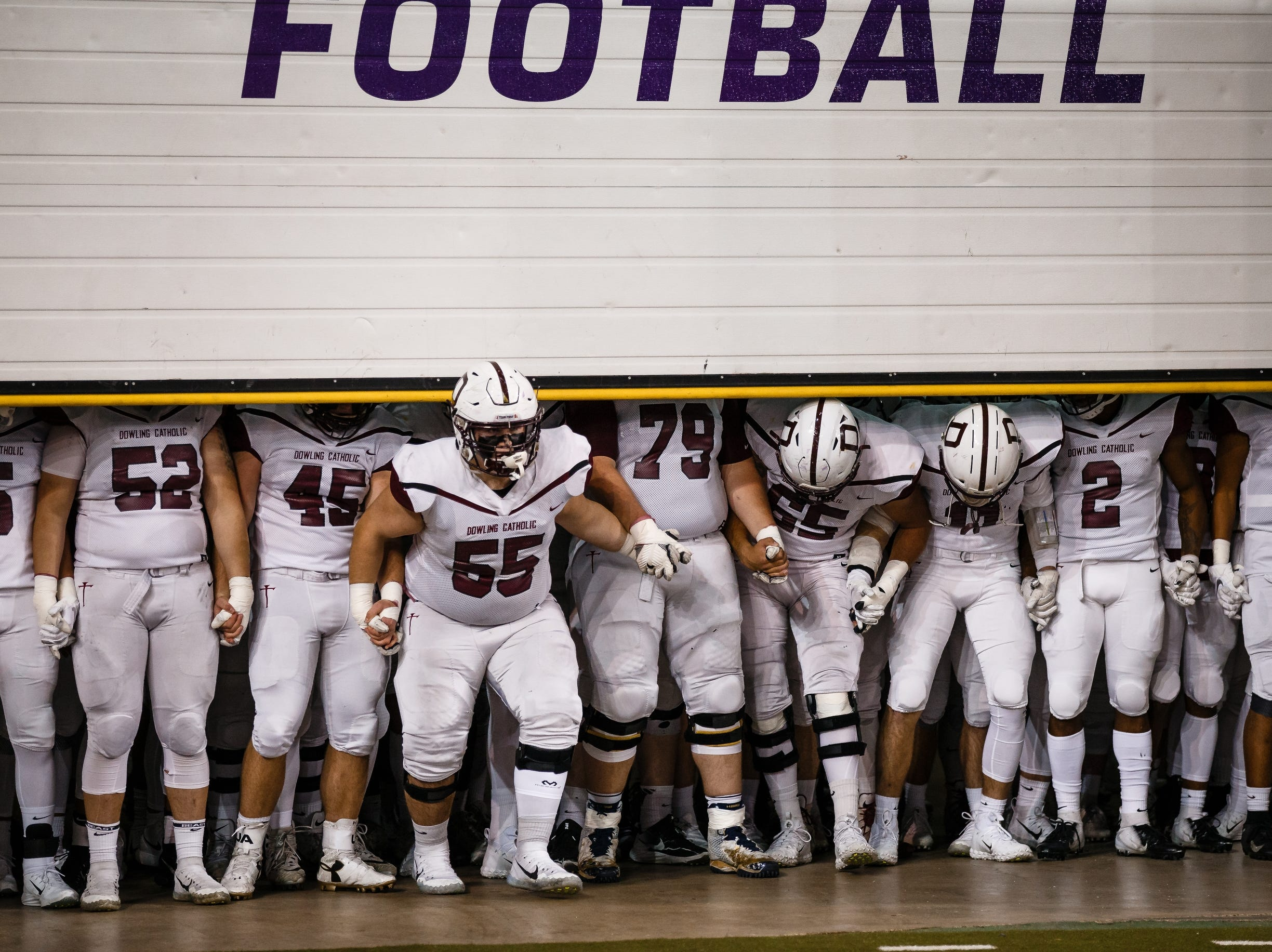 Dowling Catholic's Alex Kirton (55) leads the Maroons out of their tunnel before their class 4A state championship football game against Cedar Falls on Friday, Nov. 16, 2018, in Cedar Falls. Cedar Falls takes a 13-7 lead into halftime.