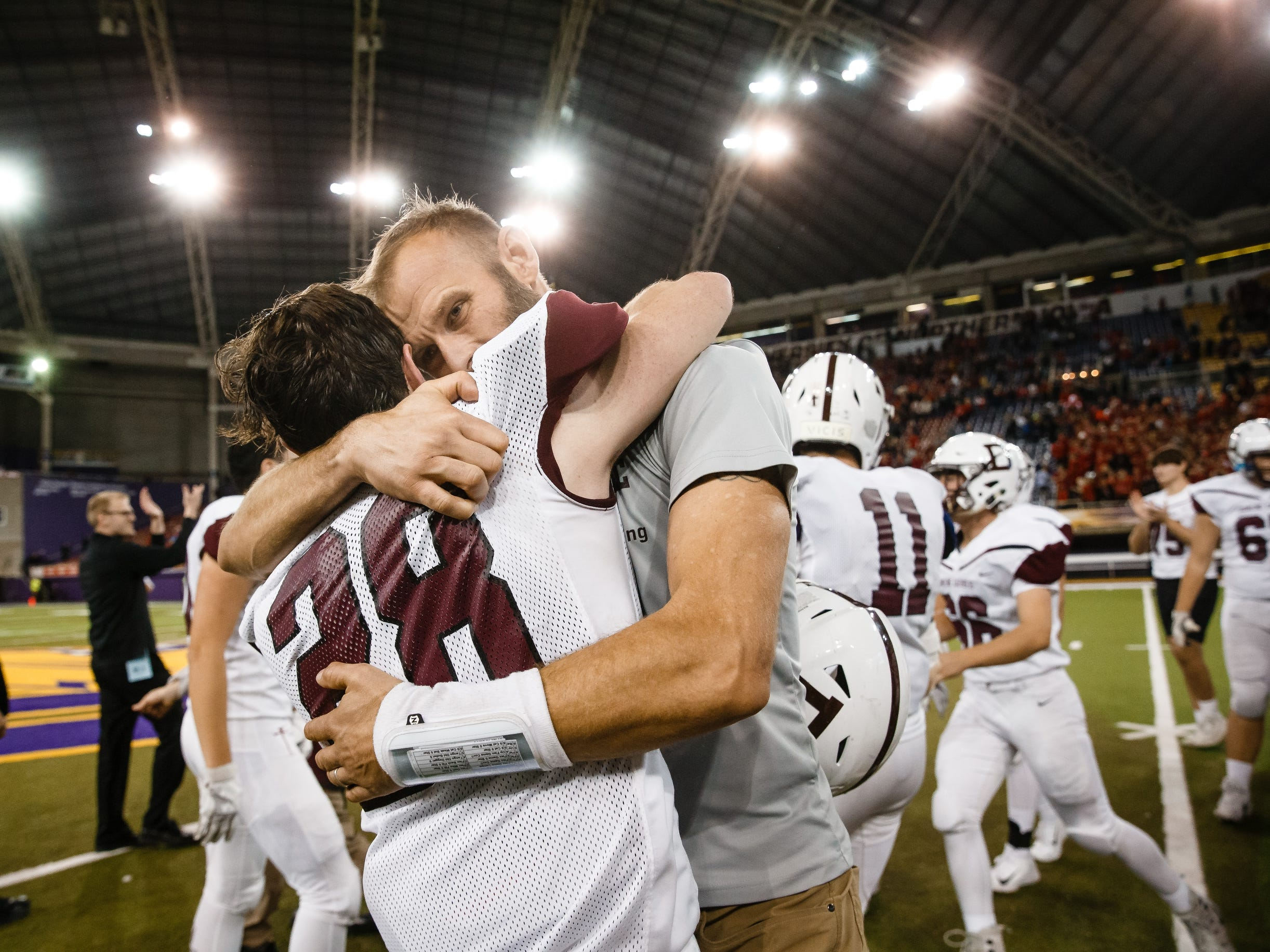 Dowling Catholic players and coaches celebrate their 22-16 victory over Cedar Falls to win the class 4A state championship football game on Friday, Nov. 16, 2018, in Cedar Falls.
