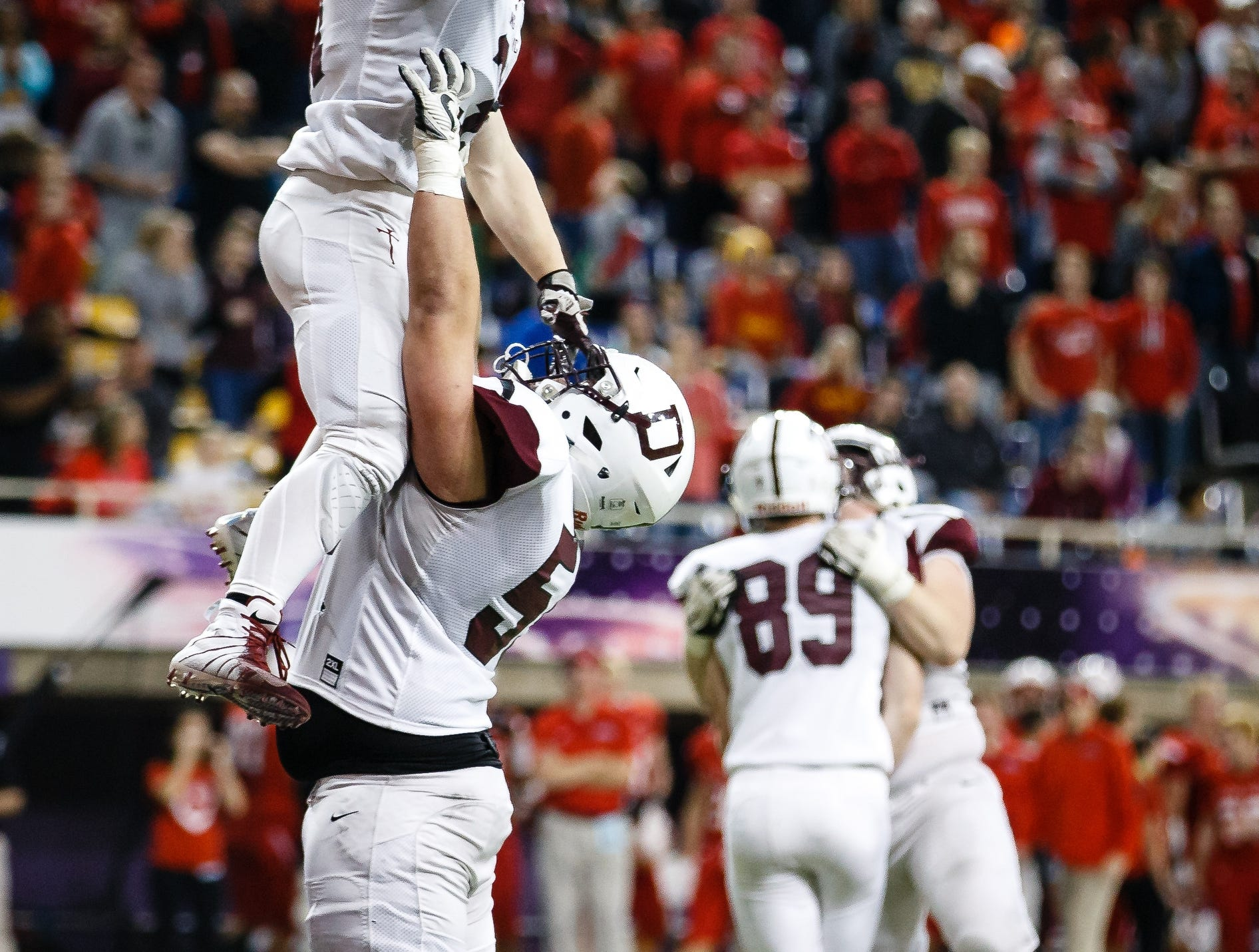 Dowling Catholic's Teagan Johnson (31) is hoisted by Dowling Catholic's Alex Kirton (55) after Johnson ran in for a touchdown making the score 13-16 during their class 4A state championship football game on Friday, Nov. 16, 2018, in Cedar Falls. Dowling Catholic would go on to defeat Cedar Falls 22-16 and win their sixth state title.